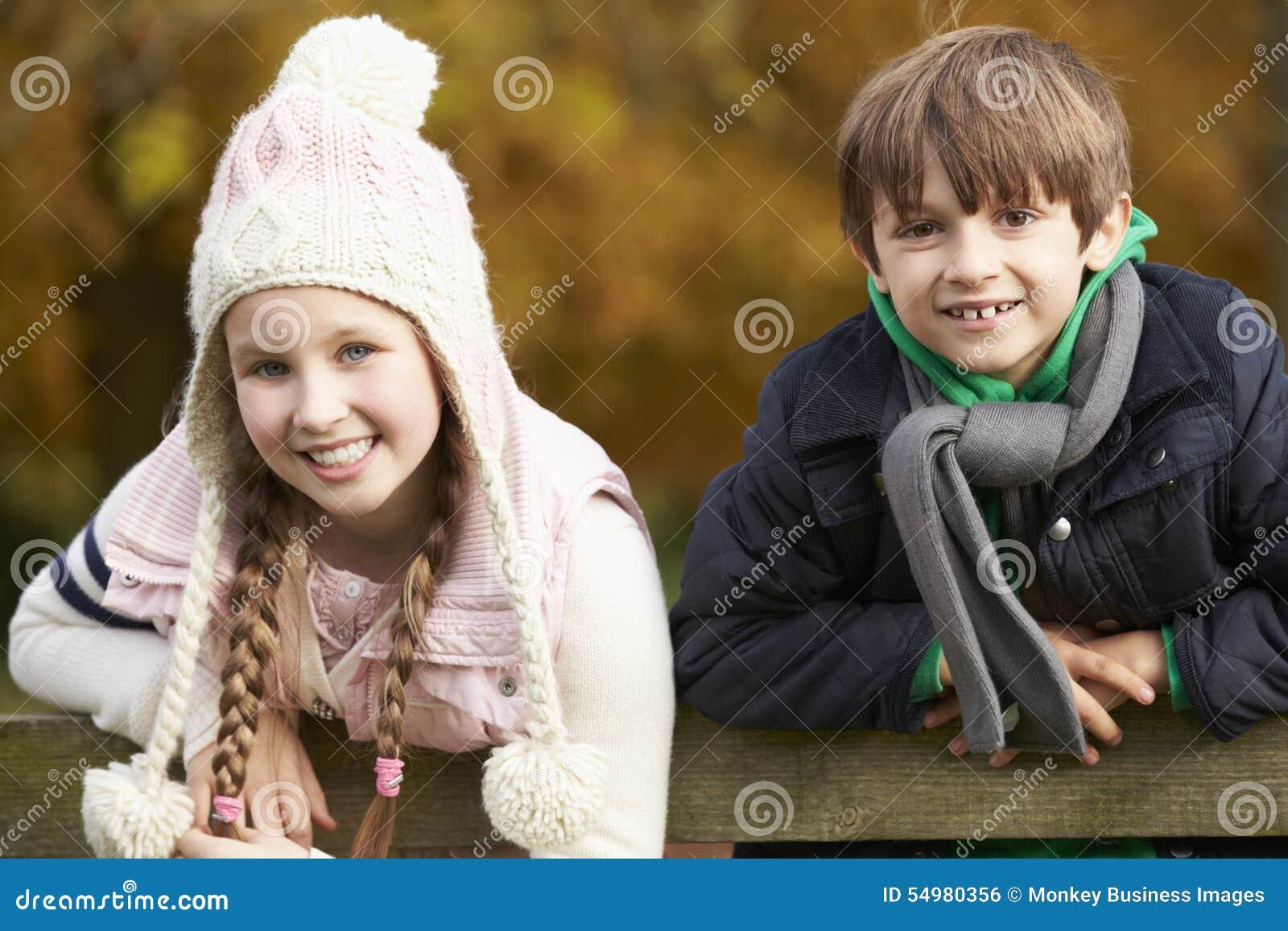Stående av två barn som lutar över trästaketet