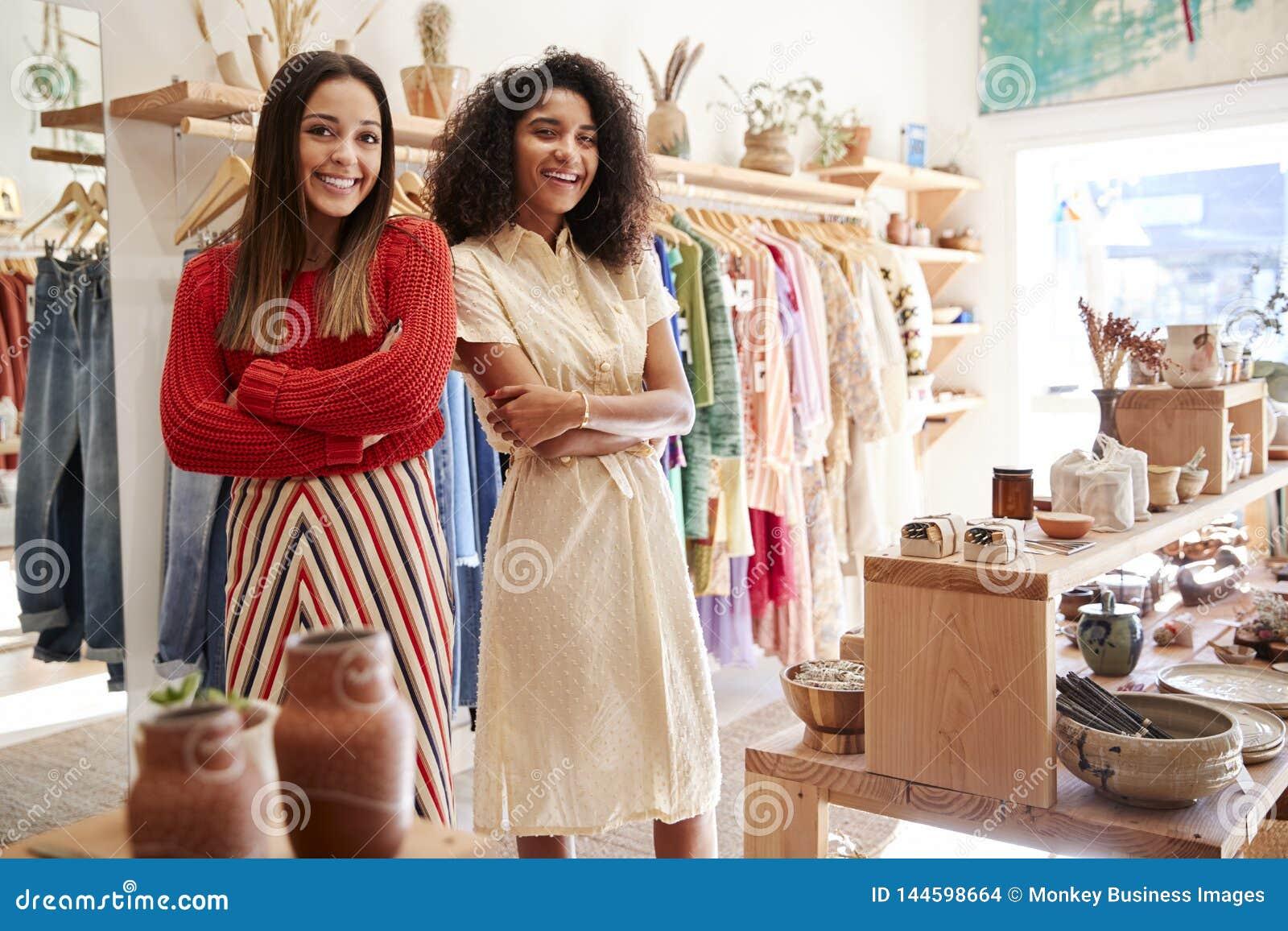 Stående av två kvinnliga försäljningsassistenter som arbetar i kläd- och gåvalager