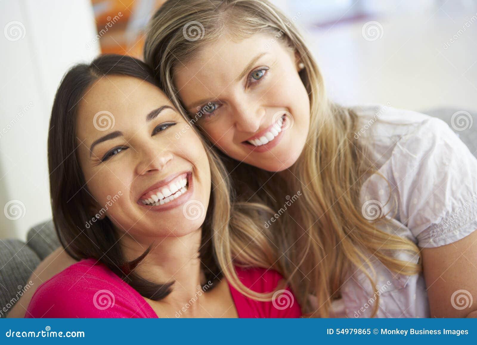 Stående av två le kvinnliga vänner på soffan