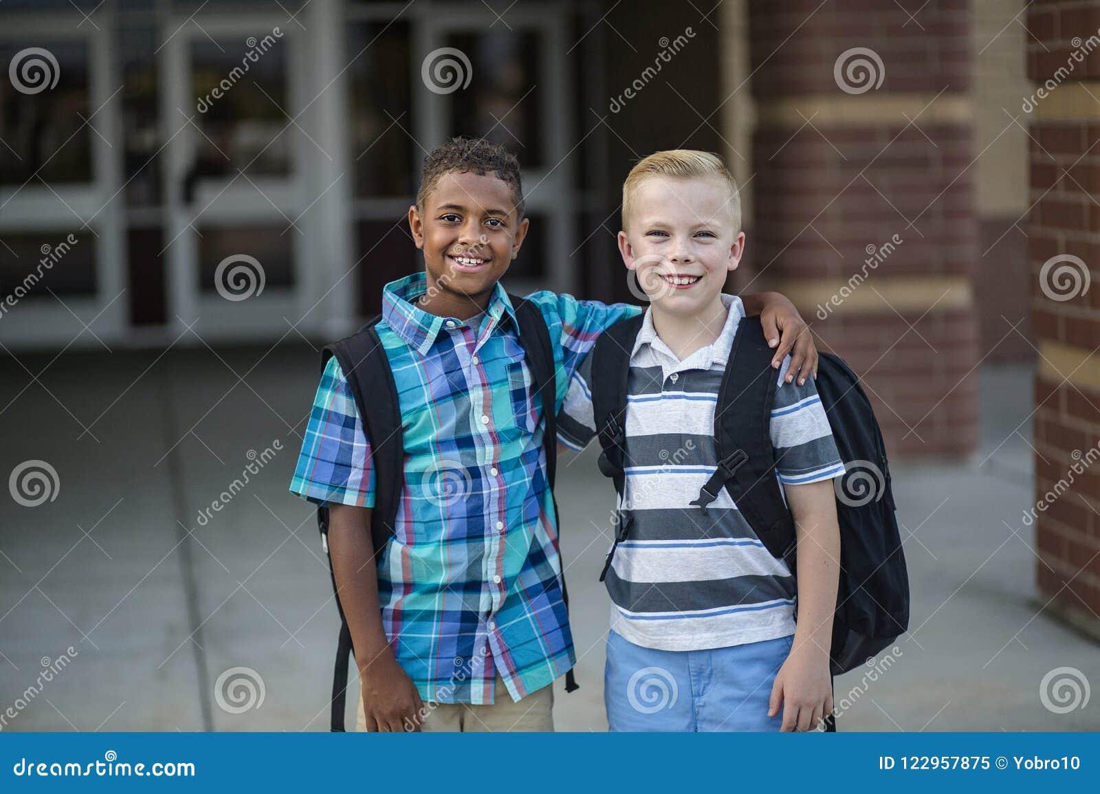 Stående av två olika skolaungar som står utanför deras grundskolabyggnad