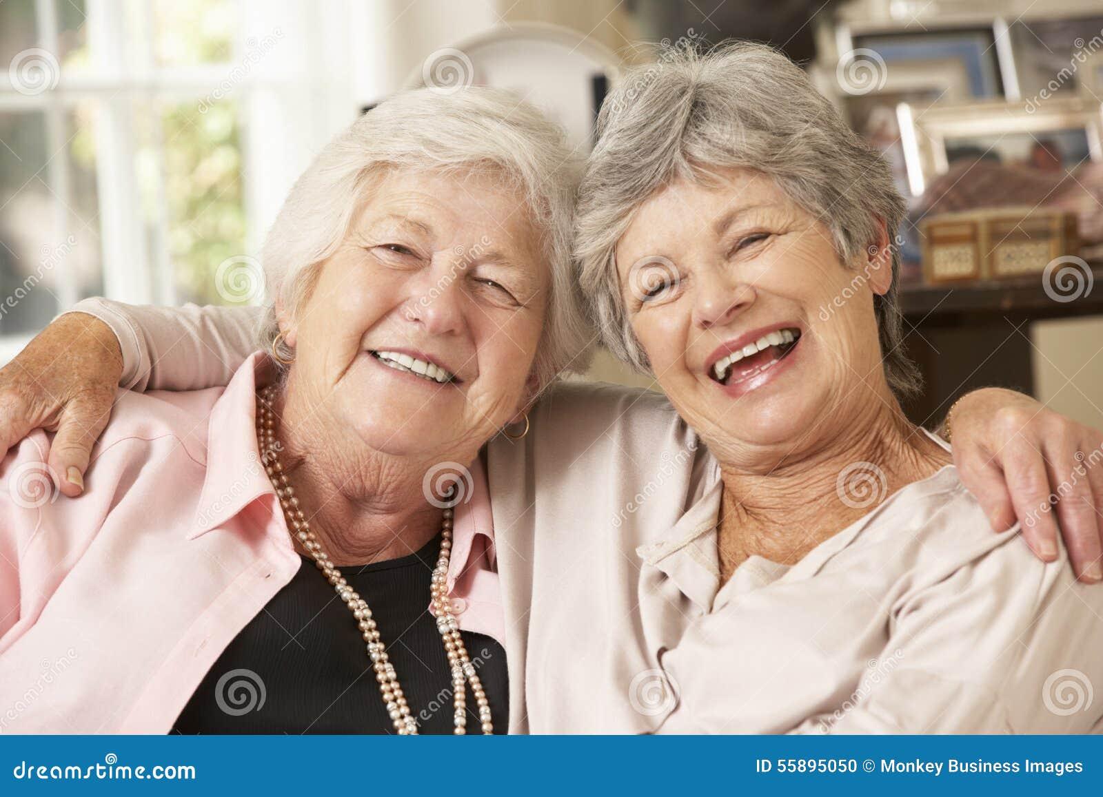 Stående av två pensionerade höga kvinnliga vänner som sitter på soffan
