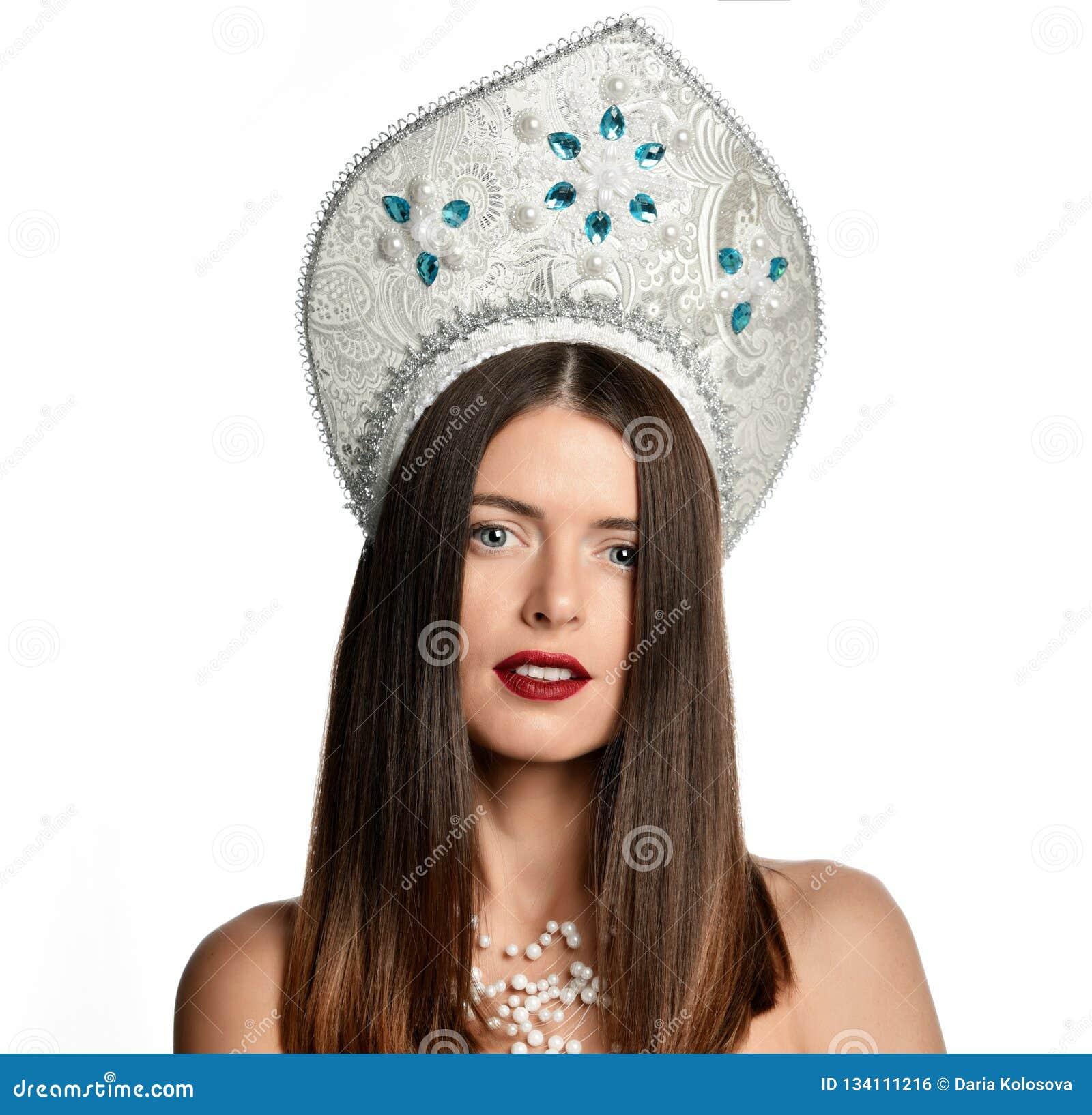 Stående av ung flickamodellen i kokoshnikhatt med naturlig isolerade makeup och långt blåsa hår se kameran