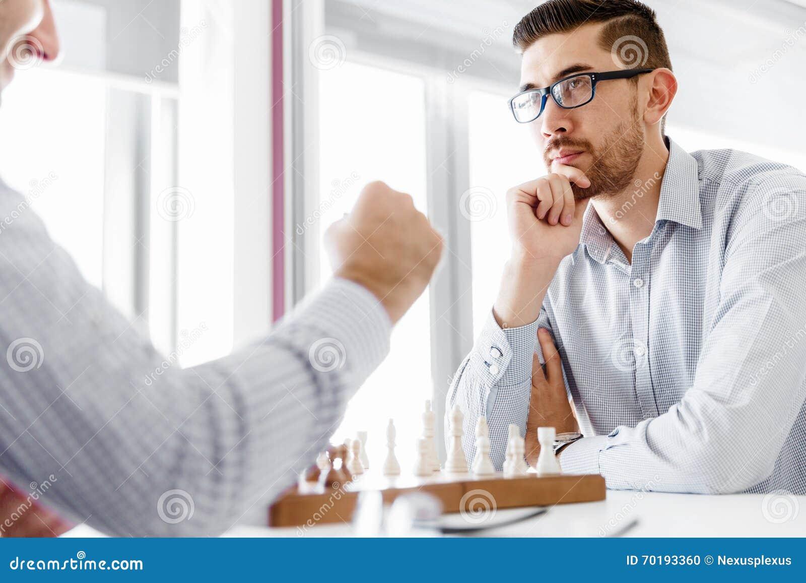 Stående av ung man som två spelar schack