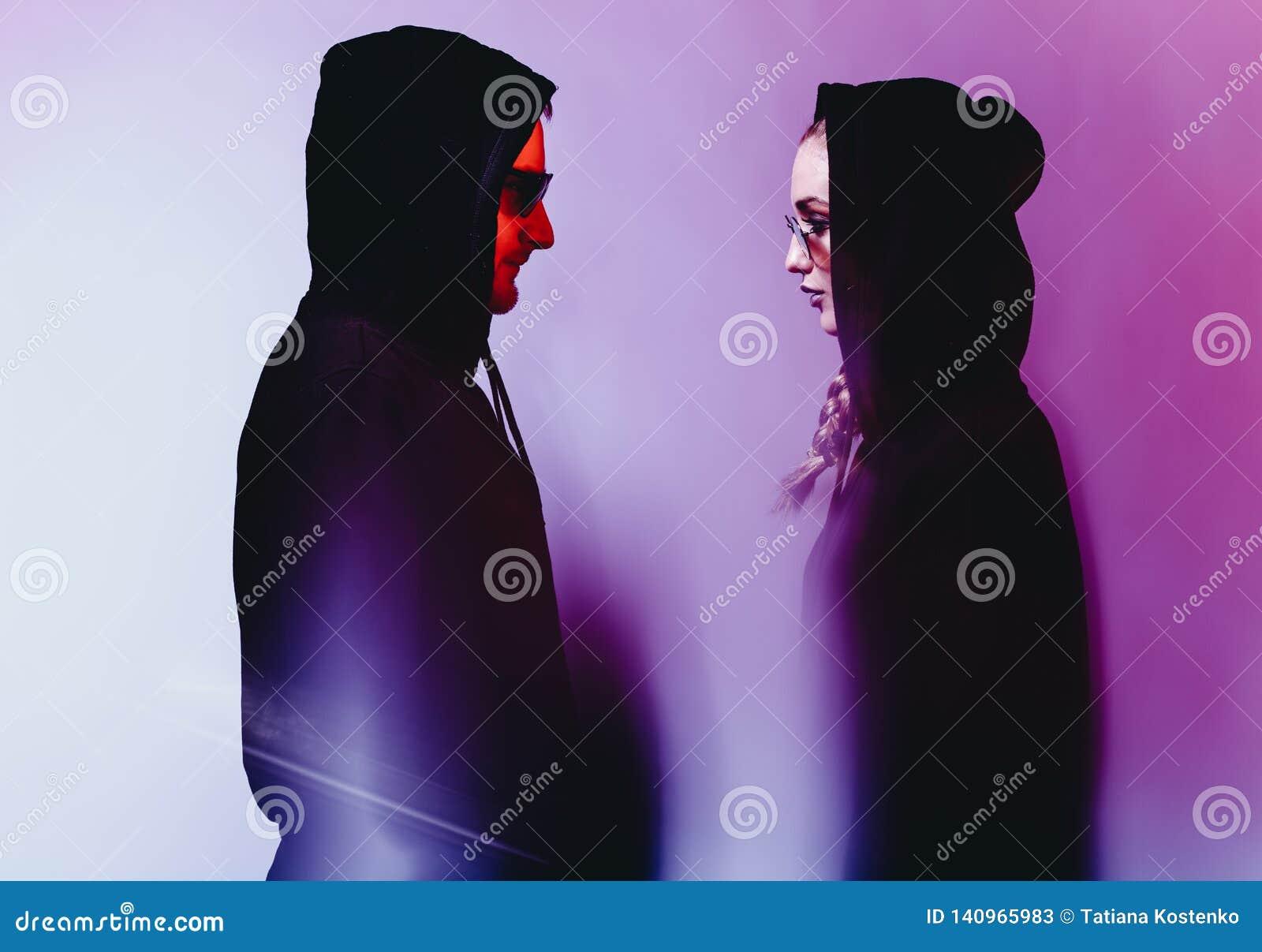 Stående av unga par för mode i en svart tröja med en huv och solglasögon i neonljus i studion