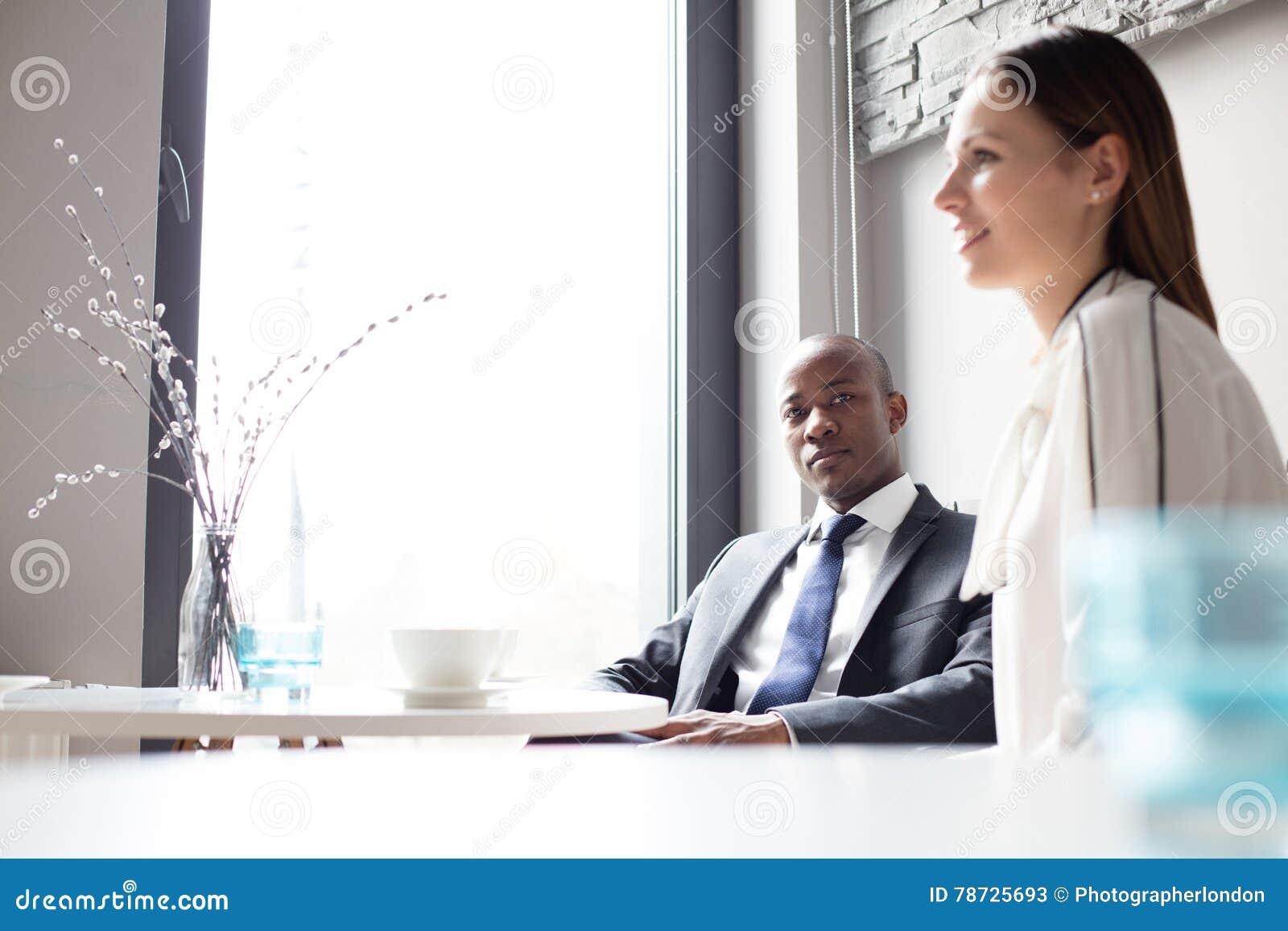 Stående av ungt affärsmansammanträde med den kvinnliga kafeterian för kollega i regeringsställning