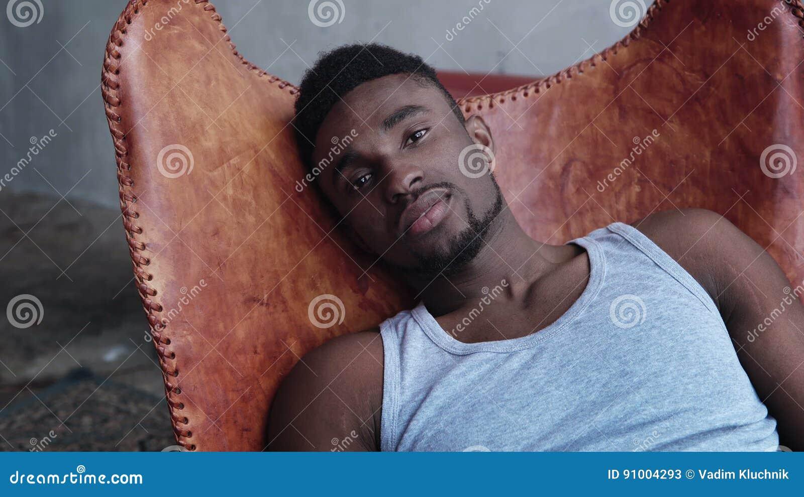 Stående av ungt stiligt afrikanskt mansammanträde på läderstolen och att se kameran Allvarlig modellman