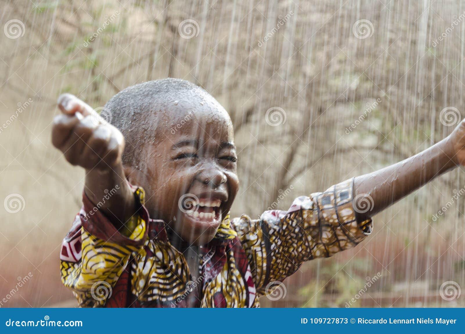 Stående det fria för liten infödd afrikansvartpojke under regnvattnet för det Afrika symbolet