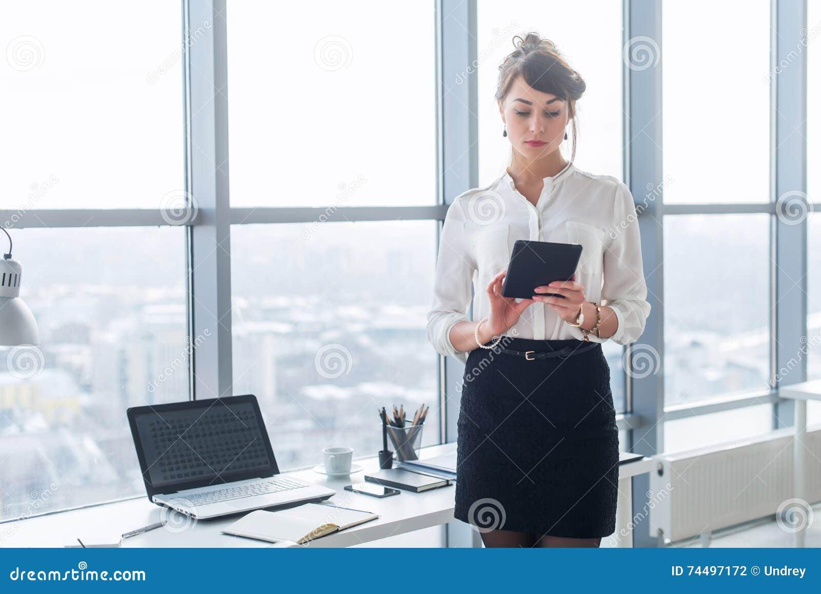 Stående för bakre sikt av en ung kvinnlig kontorsarbetare som använder apps på hennes minnestavladator, bärande formell dräkt som