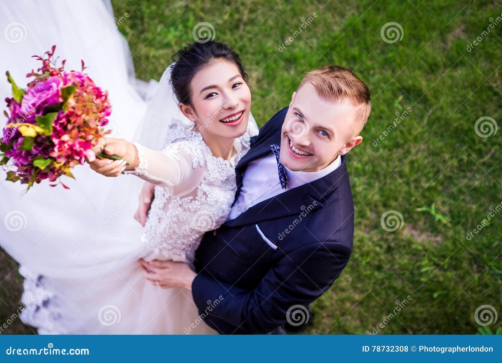 Stående för hög vinkel av det gladlynta bröllopparanseendet på gräs- fält