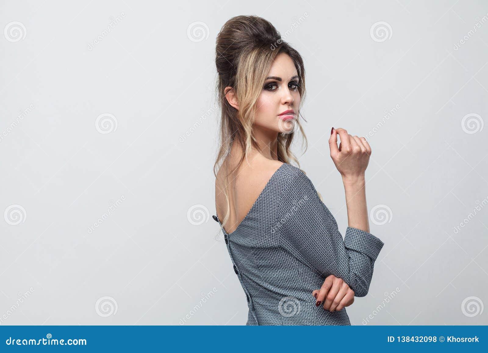 Stående för sidoprofilsikt av den härliga attraktiva modemodellen i grå klänning med makeup och frisyren som står som poserar och