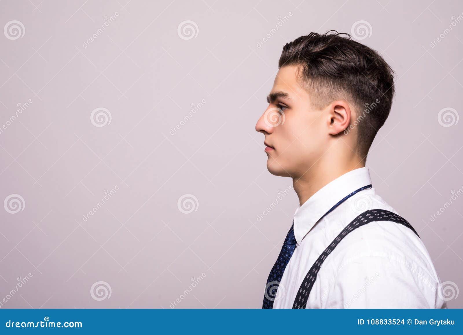 Stående för sidosikt av den säkra mannen med den härliga frisyren i den vita skjortan som ser på kopieringsutrymme som isoleras p