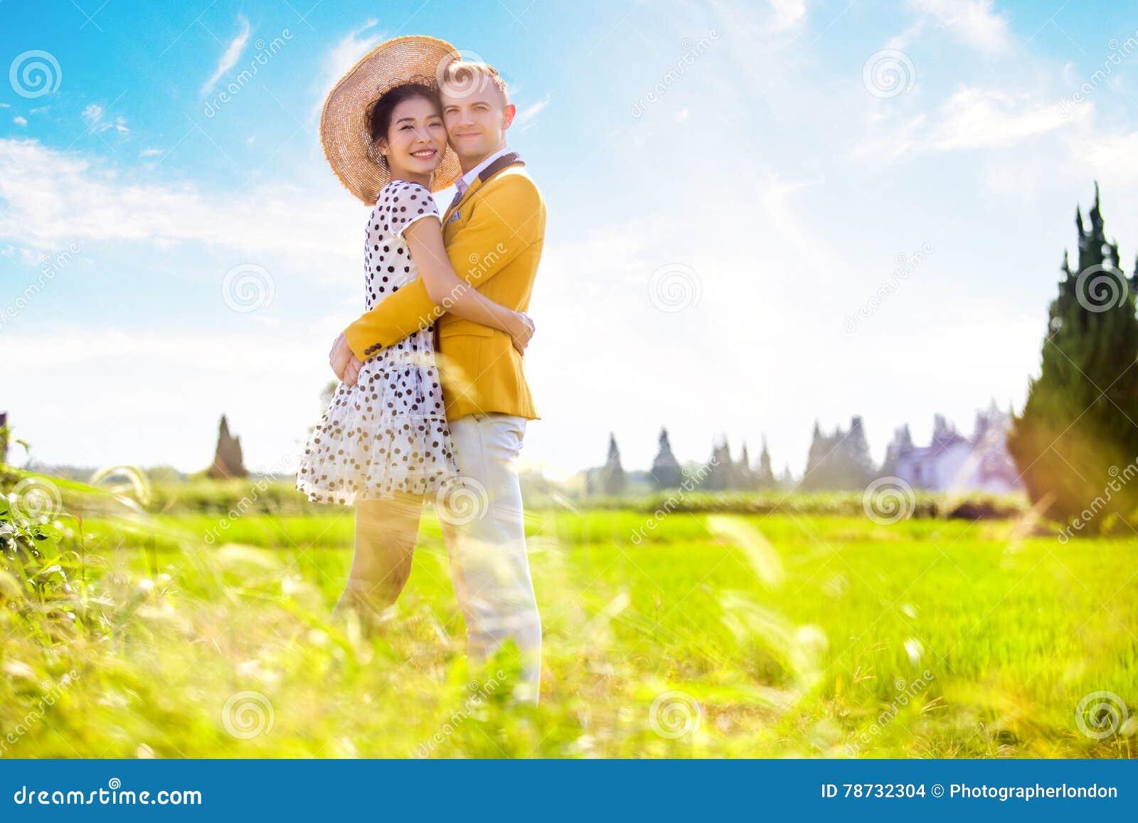 Stående för sidosikt av romantiska par som omfamnar på fält