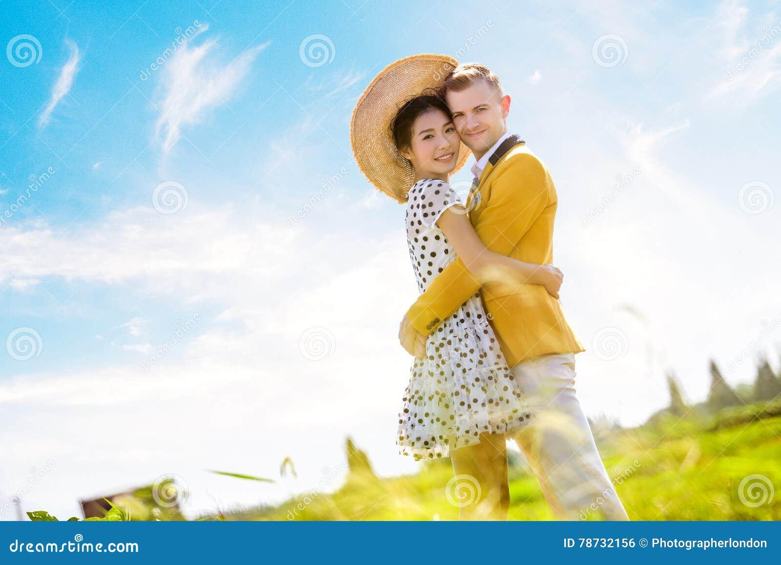 Stående för sidosikt av romantiska par som omfamnar på fält mot himmel