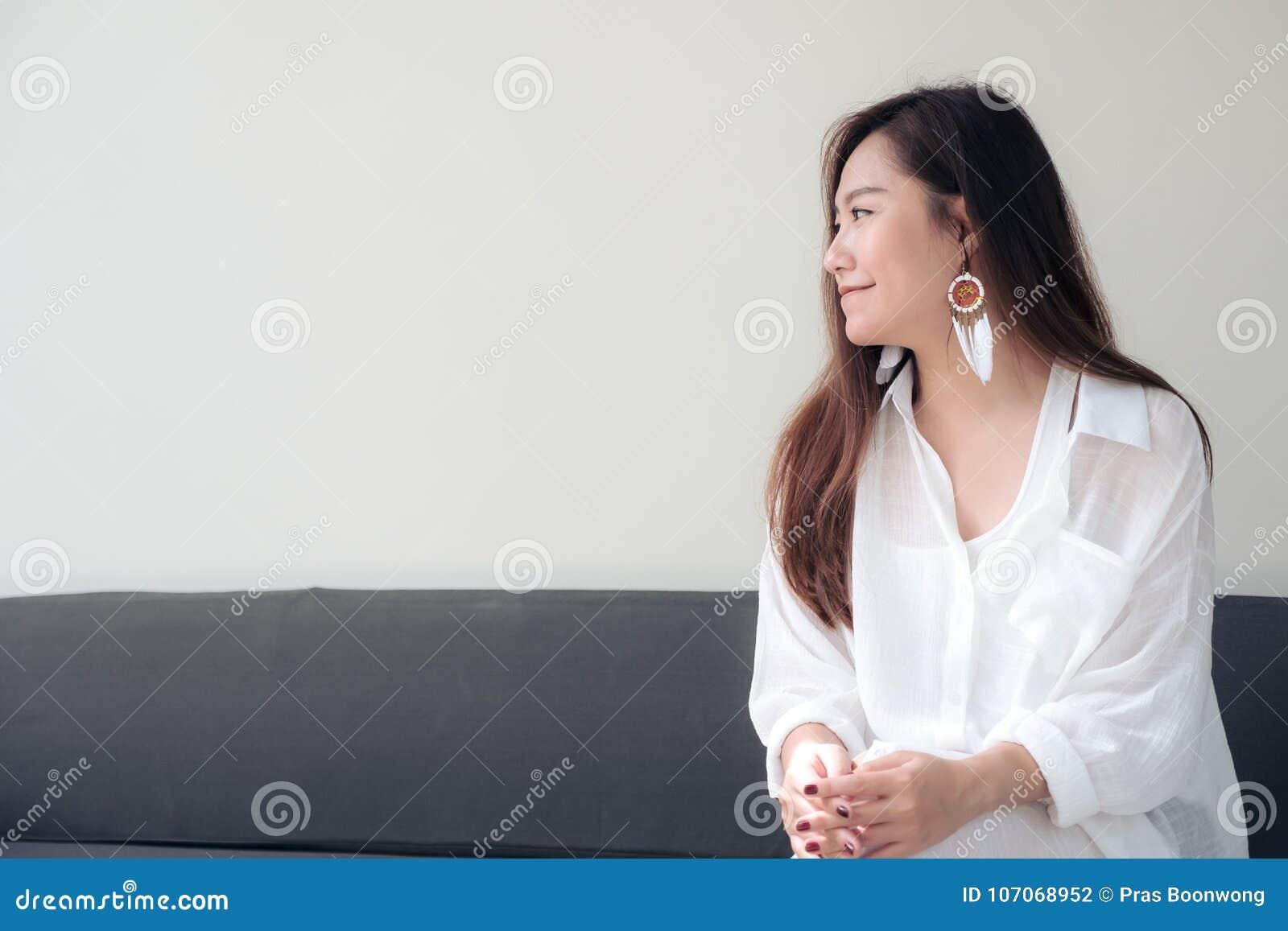 Ståendebild av en härlig asiatisk kvinna på vitt klänningsammanträde med mening lyckligt