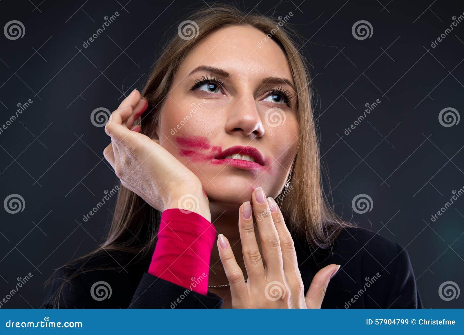 Ståendekvinna med smetad läppstift som ser upp