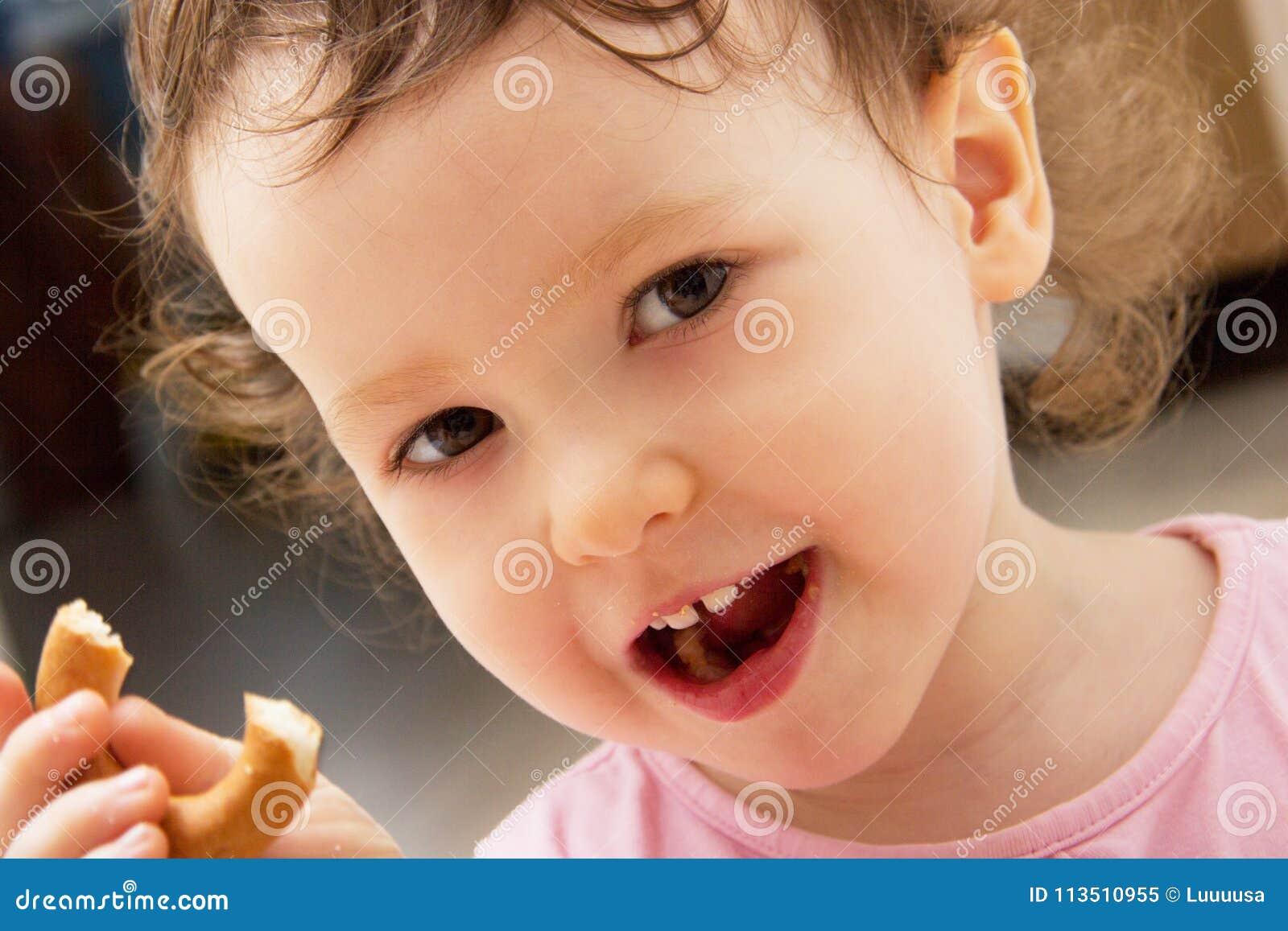 Ståenden av åriga två behandla som ett barn flickan Det lockiga barnet äter en bagel och ler Två framtänder är synliga Halva-äten