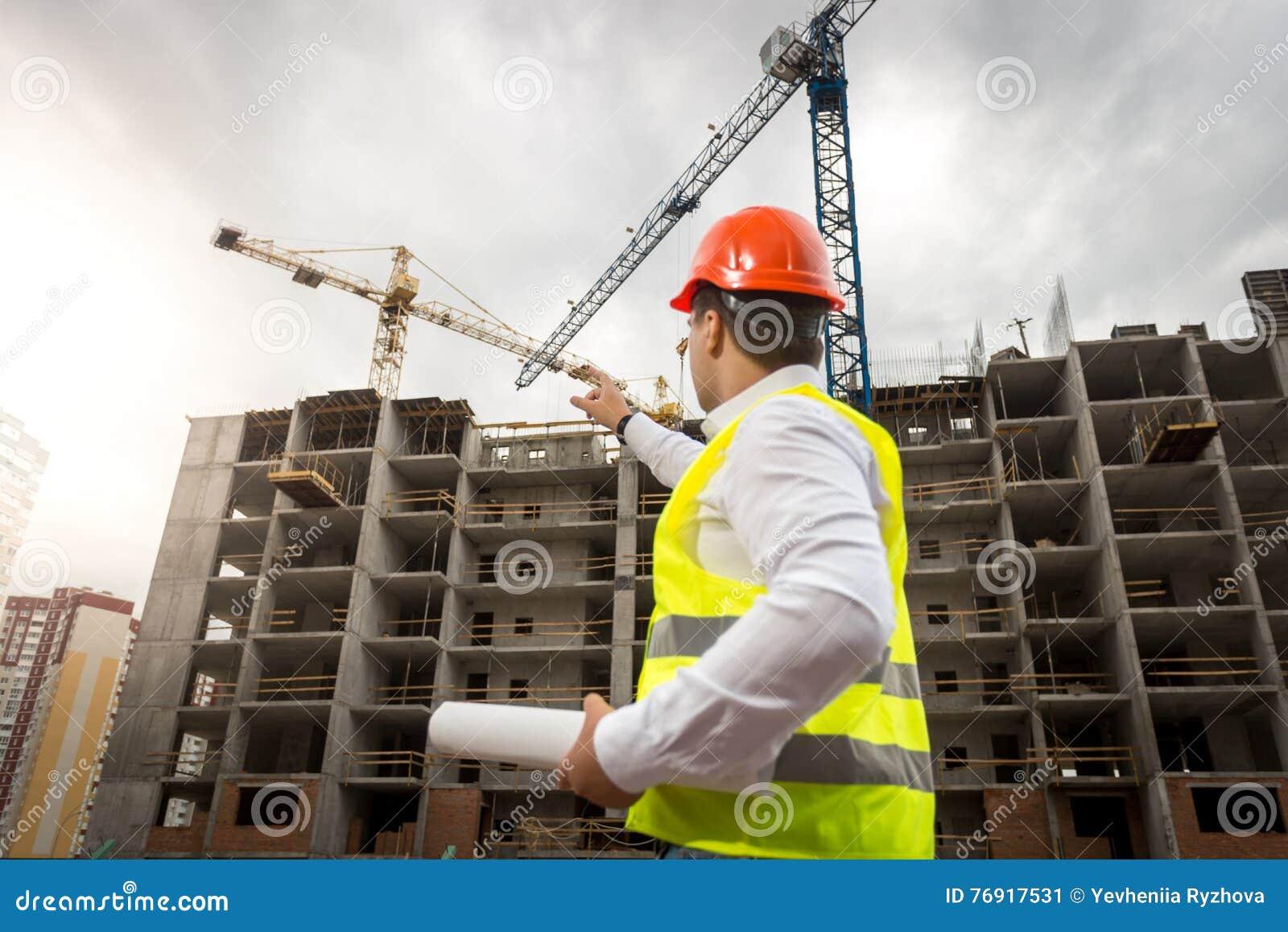Ståenden av arkitektinnehavet gör en skiss av och peka på buildin