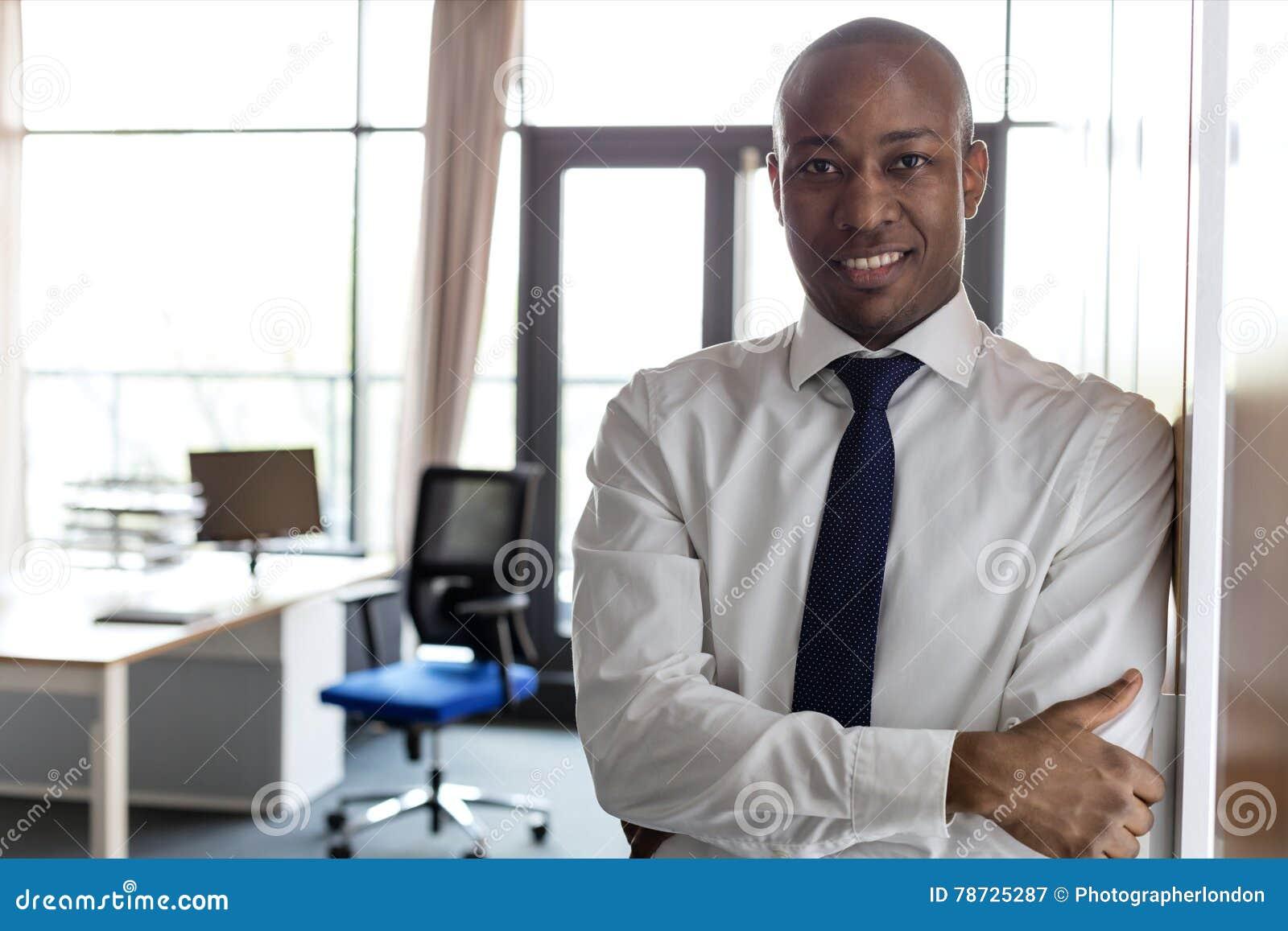 Ståenden av att le den unga affärsmannen med armar korsade benägenhet på skåp i regeringsställning