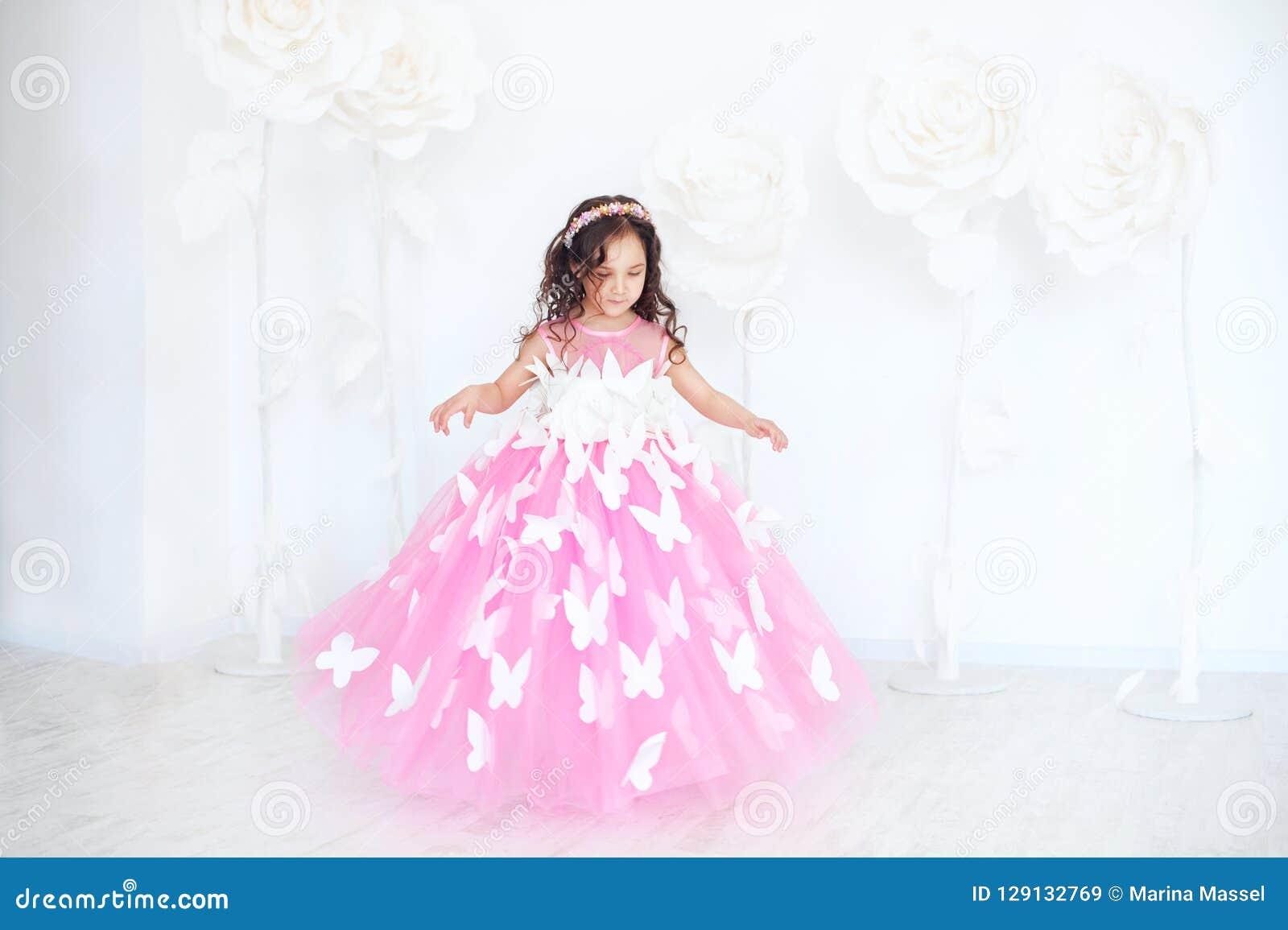 Ståenden av att le lilla flickan i prinsessarosa färger klär med fjärilar