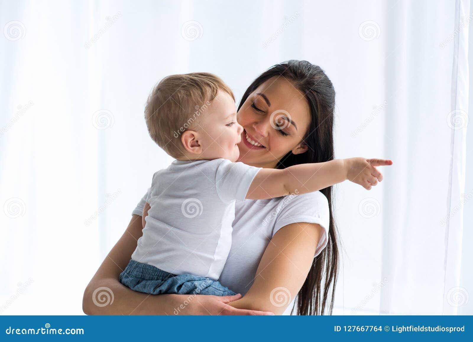 Ståenden av att le modern med förtjusande behandla som ett barn i händer som bort pekar