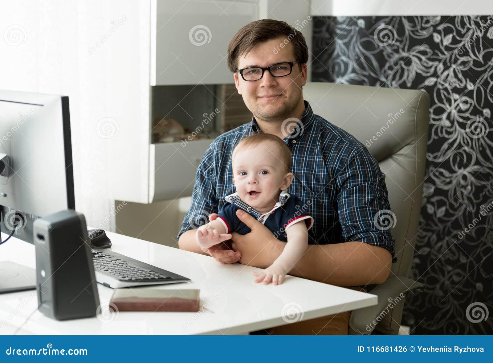 Ståenden av att le ungt manligt freelancersammanträde i inrikesdepartementet och innehavet hans åriga 1 behandla som ett barn son
