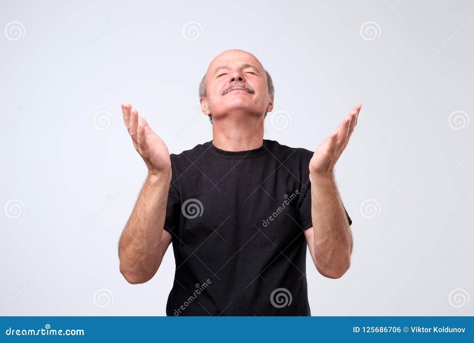 Ståenden av att tigga den caucasian mannen i tillfällig dräkt och att rymma händer ber in och förhoppningsvis se upp och att be