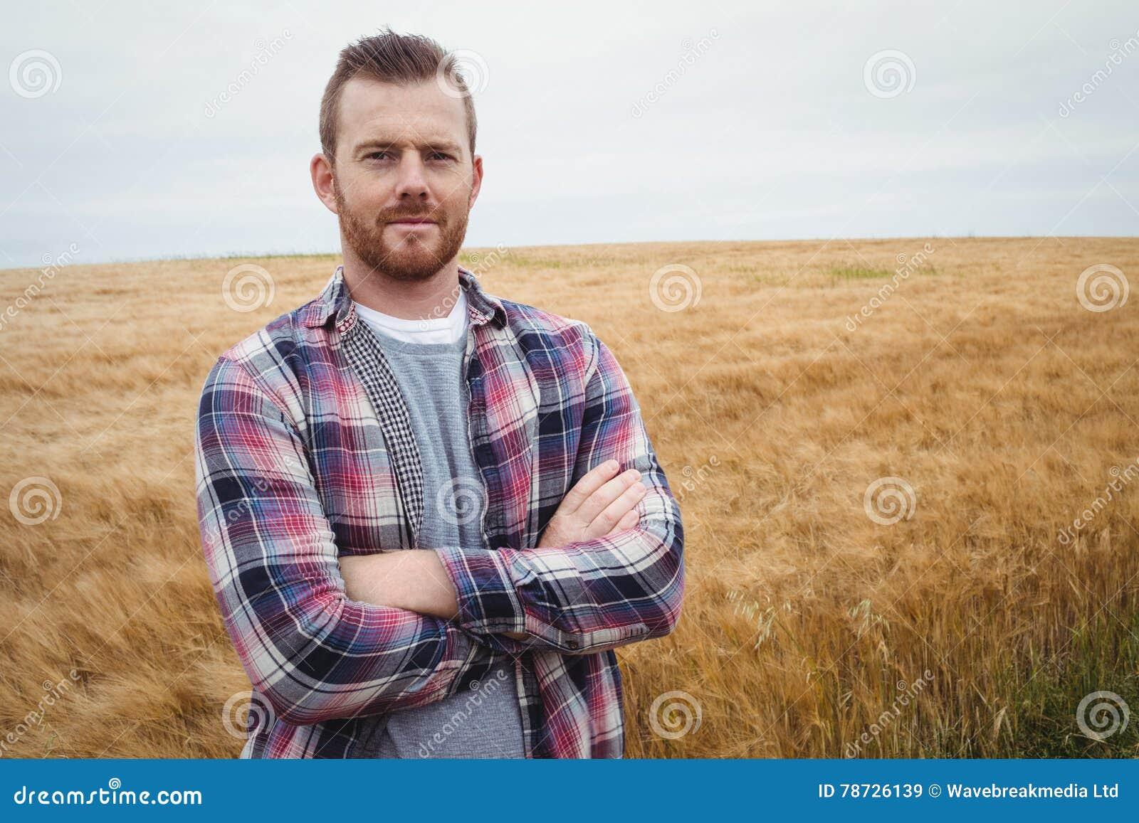 Ståenden av bondeanseendet med armar korsade i fältet