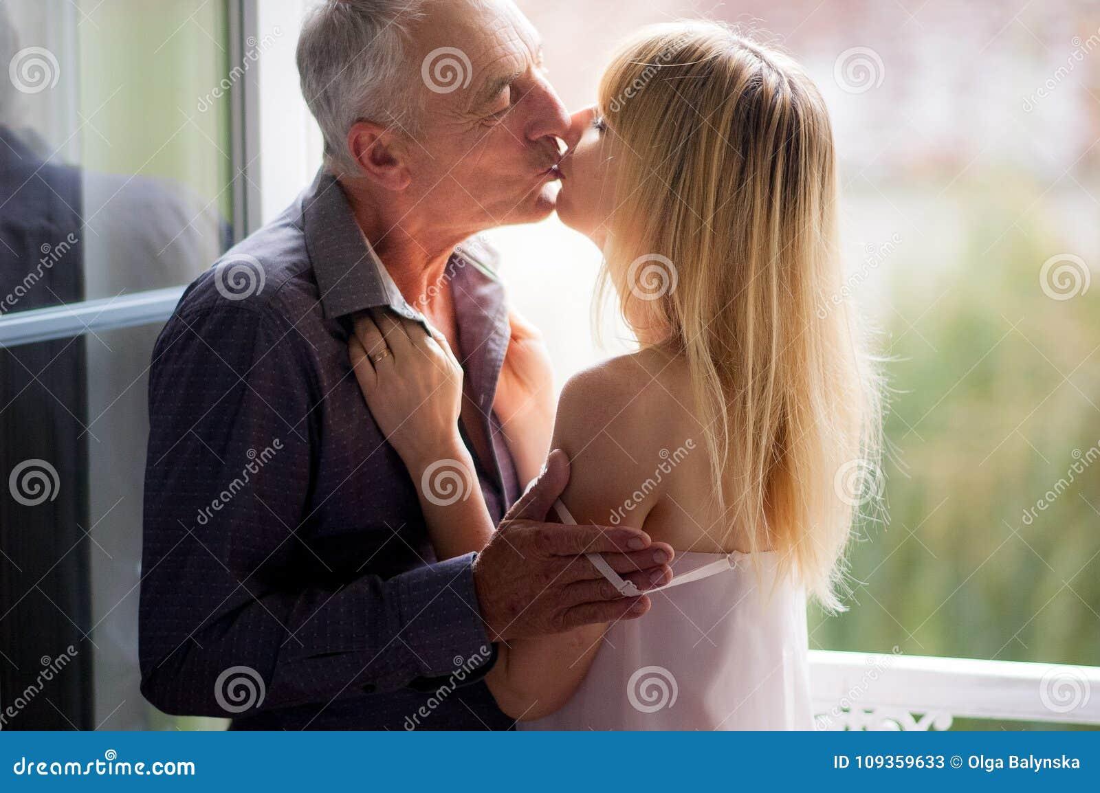Ståenden av den attraktiva unga kvinnan som kysser hennes höga make nära, öppnade Windows i rummet under sommar Tid åldrades