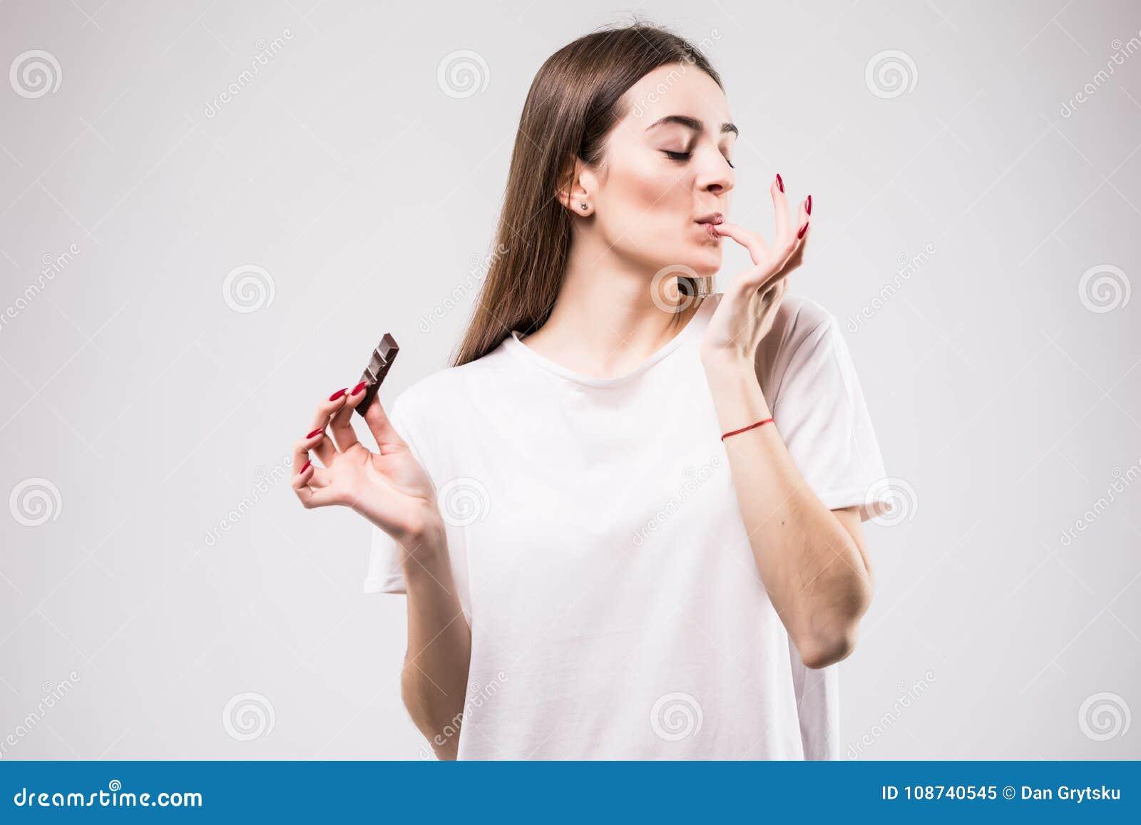 Ståenden av den härliga le kvinnan tycker om att äta choklad som isoleras på grå bakgrund band för mått för äpplebegreppshälsa