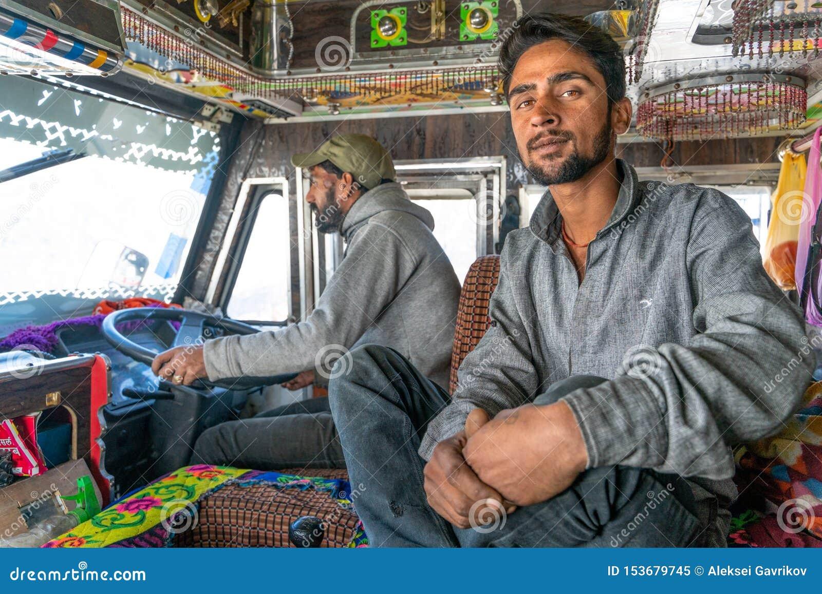 Ståenden av den indiska lastbilsföraren och hans hjälpreda