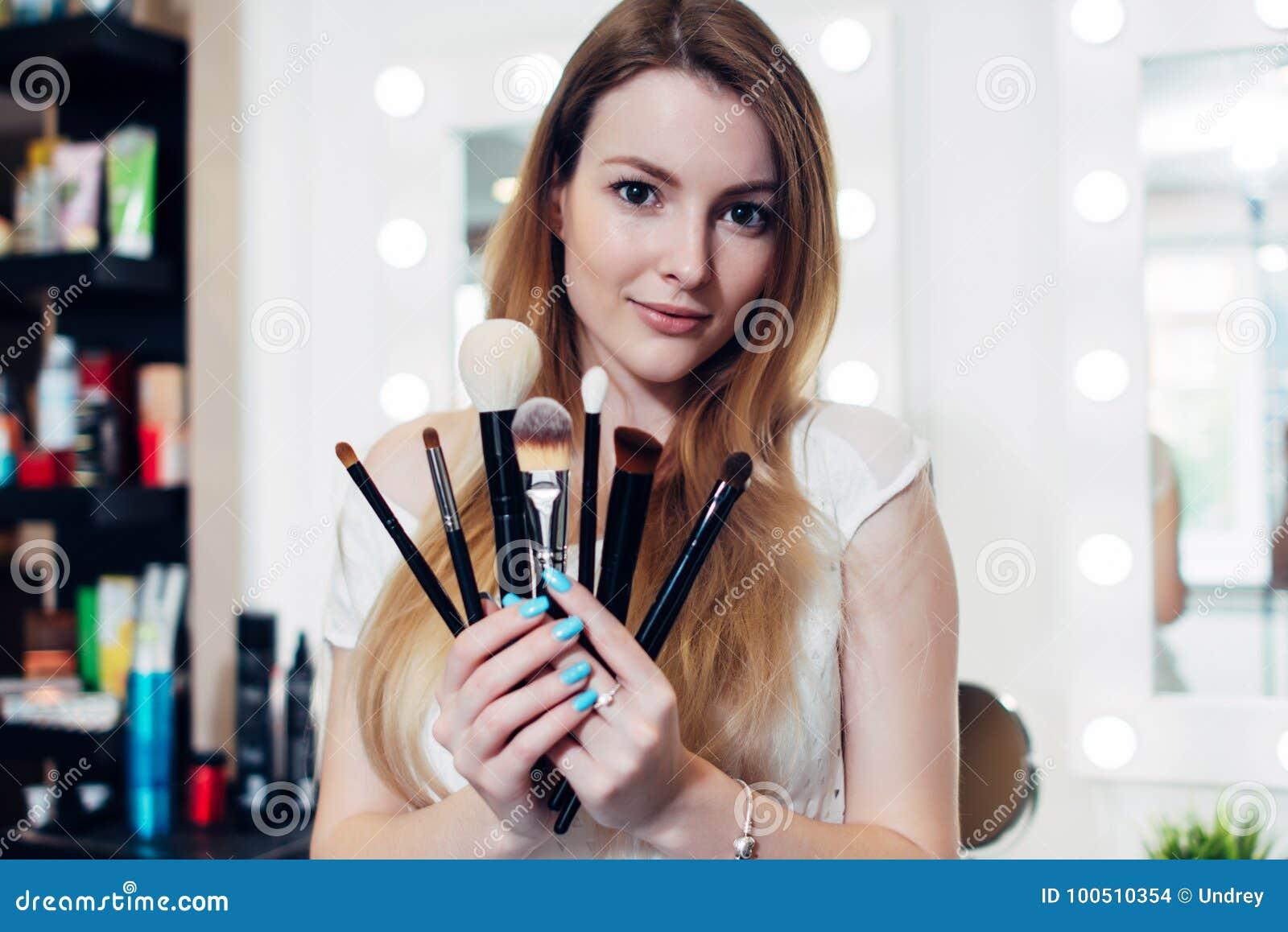 Ståenden av den kvinnliga kosmetologen som rymmer en uppsättning av makeup, borstar i skönhetsalong