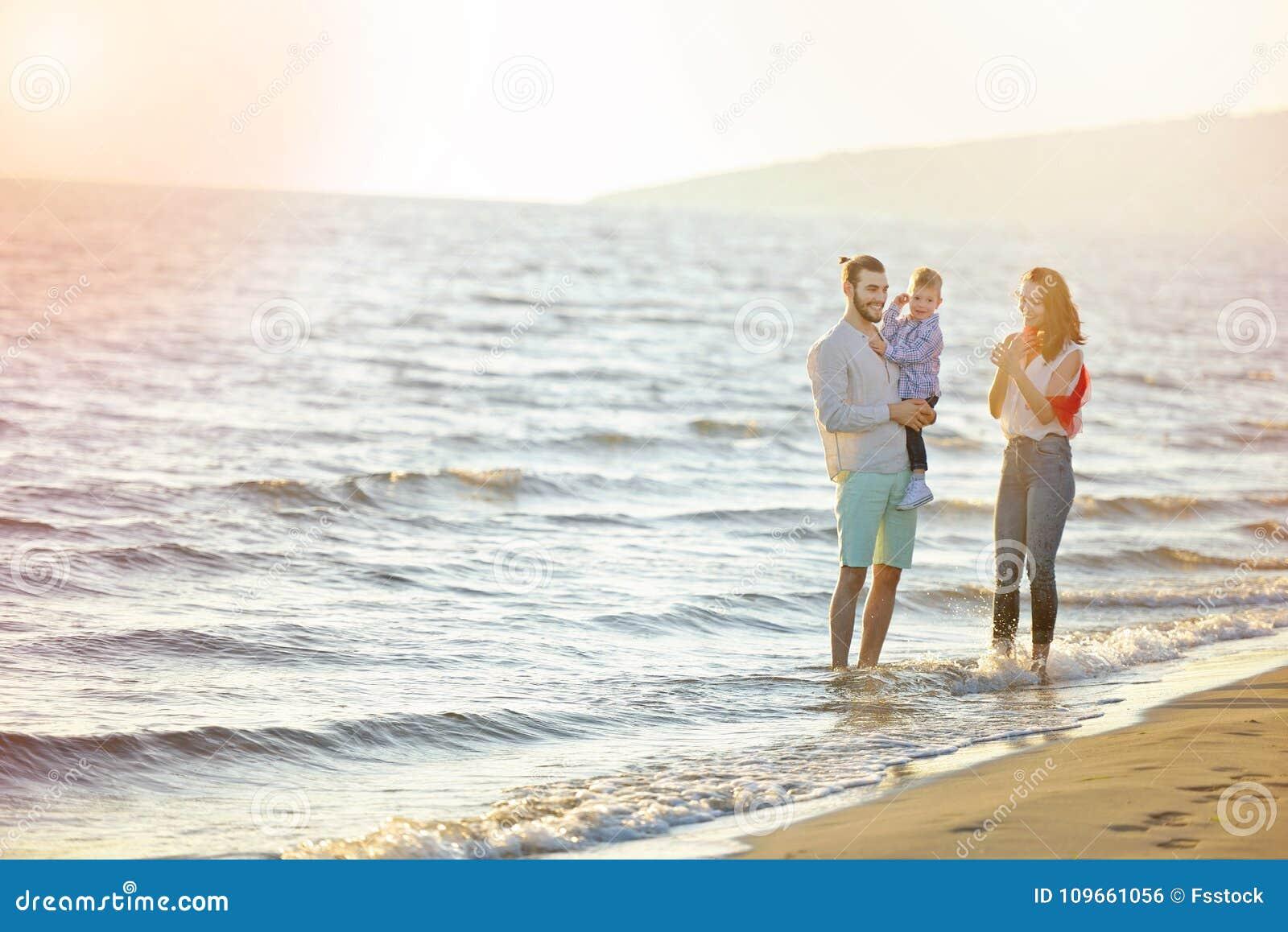 Ståenden av den lyckliga familjen och behandla som ett barn tycka om solnedgång i sommarfritiden