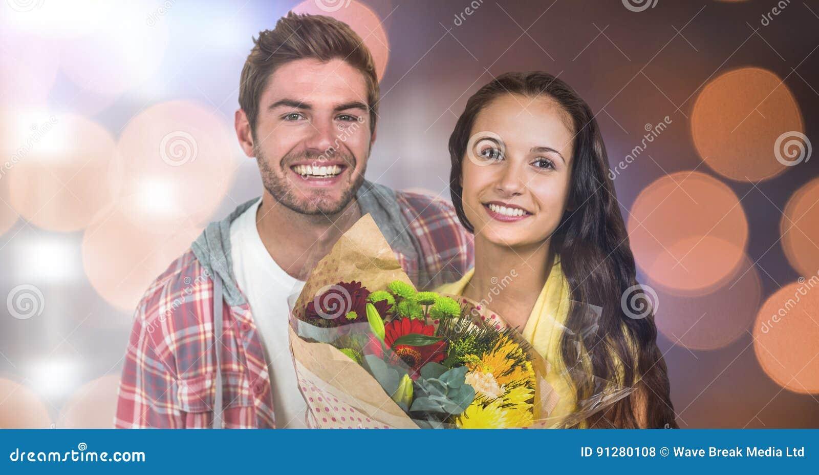 Ståenden av den lyckliga mannen av kvinnainnehavet blommar över bokeh