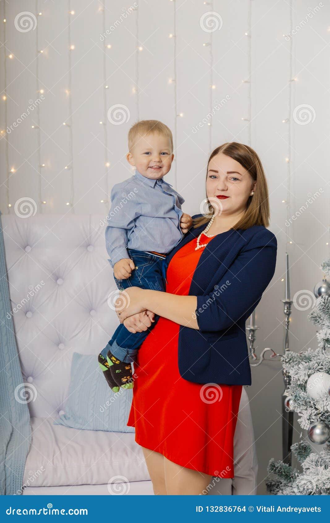 Ståenden av den lyckliga modern och förtjusande behandla som ett barn firar jul Ferier för ` s för nytt år Litet barn med mamman