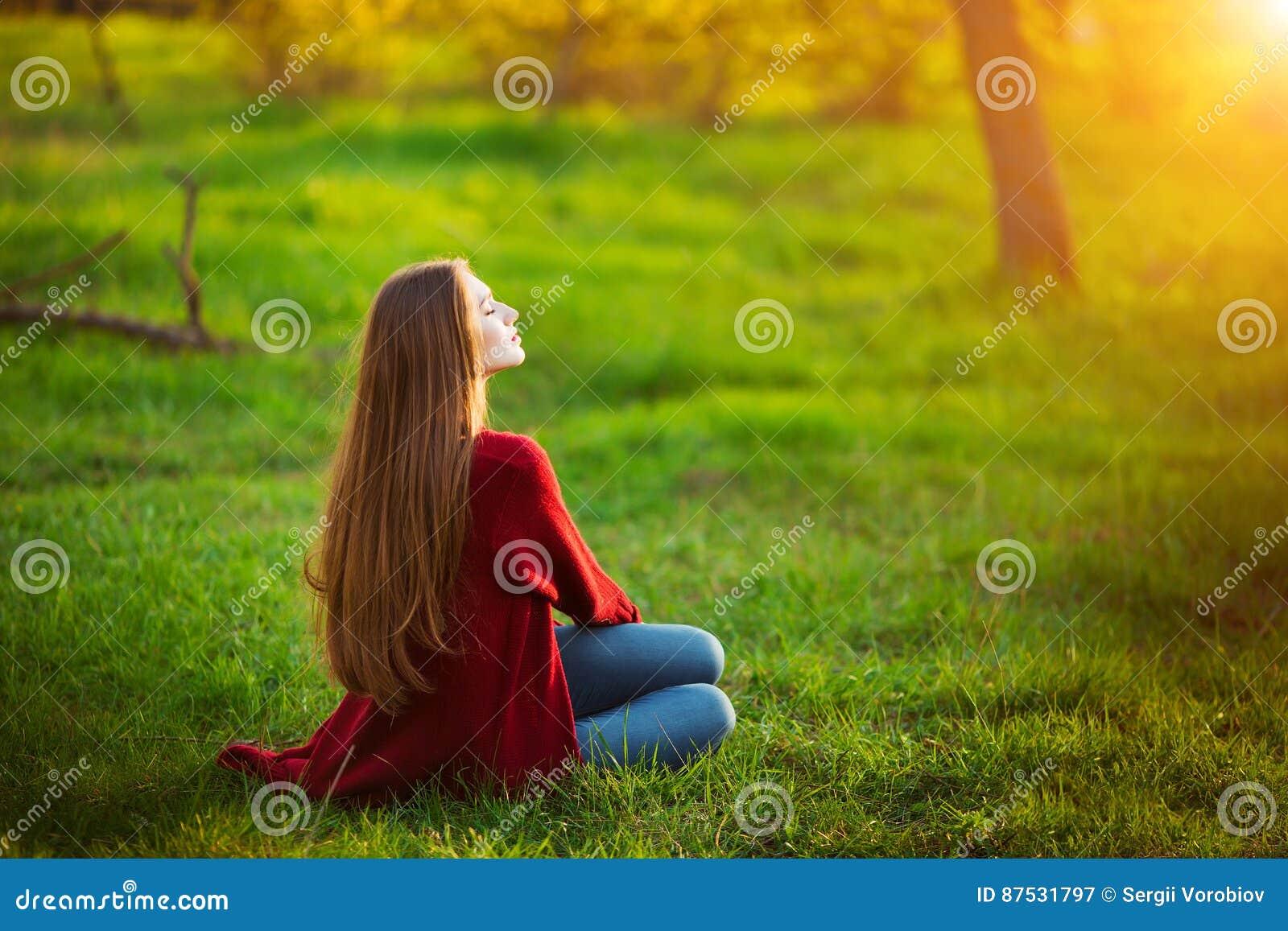 Ståenden av den lyckliga sportiga kvinnan som in kopplar av, parkerar på grön äng Glad kvinnlig modell som utomhus andas ny luft