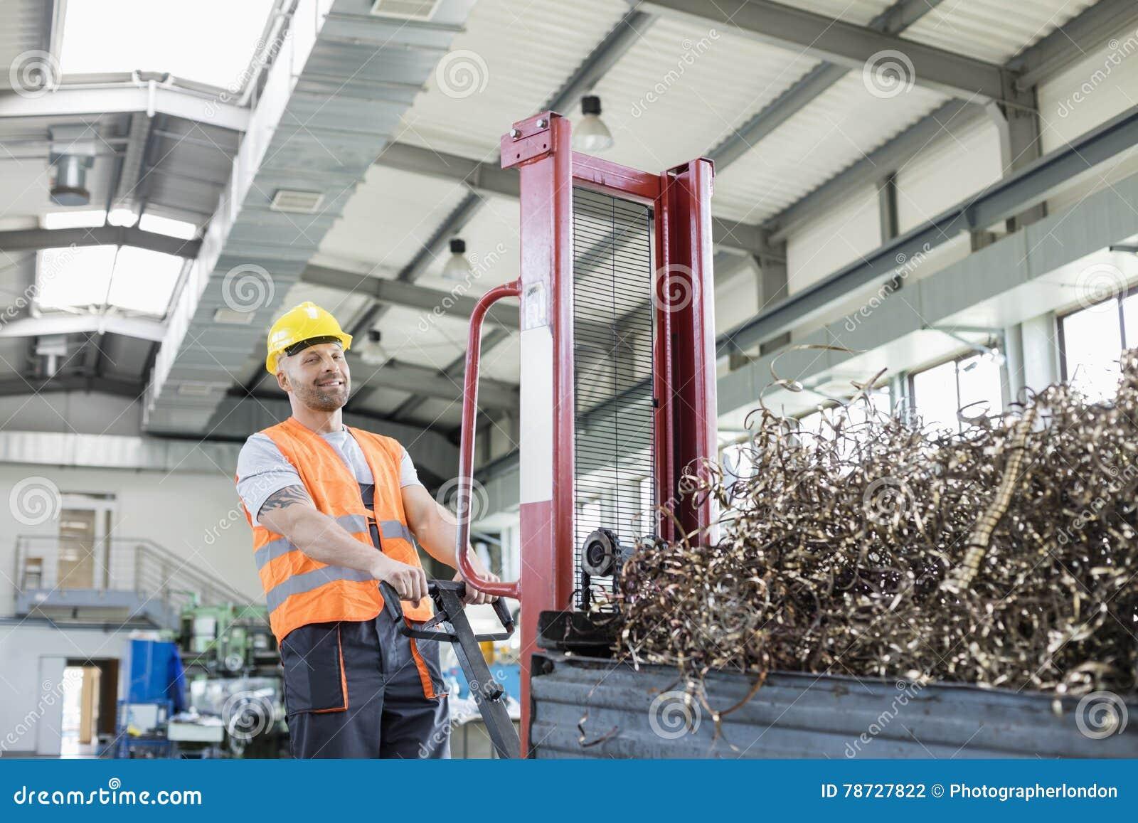 Ståenden av den mitt- vuxna arbetaren som drar handlastbilen, laddade med stålshavings i fabrik