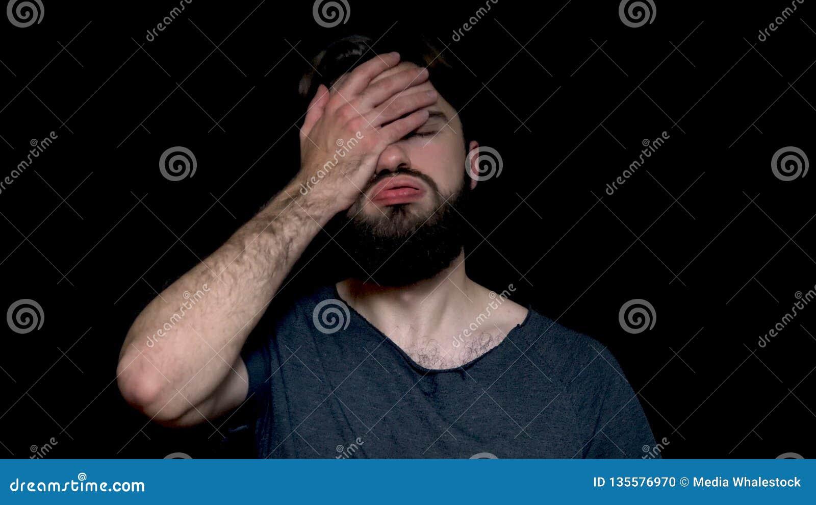 Ståenden av den svek upprivna mannen med skägget, som täcker hans framsida med, gömma i handflatan, isolerat på svart bakgrund be