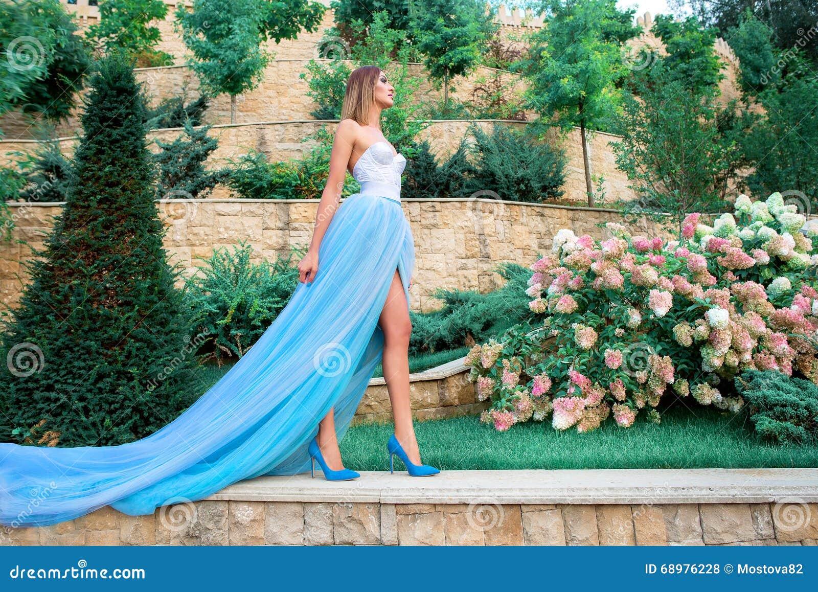 Ståenden av den unga beautilulkvinnan i långa blått klär