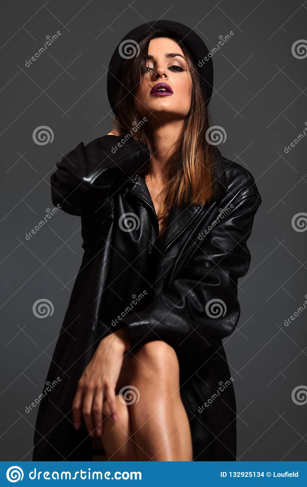 Ståenden av den unga kvinnan i svart piskar omslaget och hatten