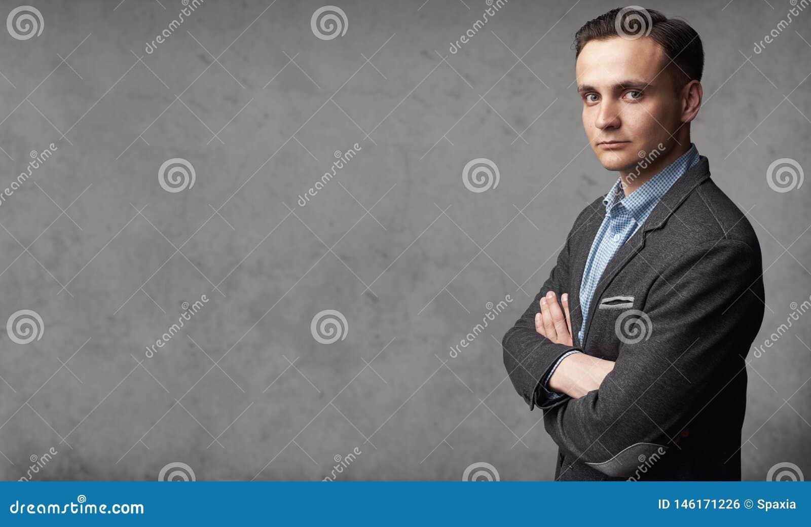Ståenden av den unga moderiktiga mannen står för grå studiovägg