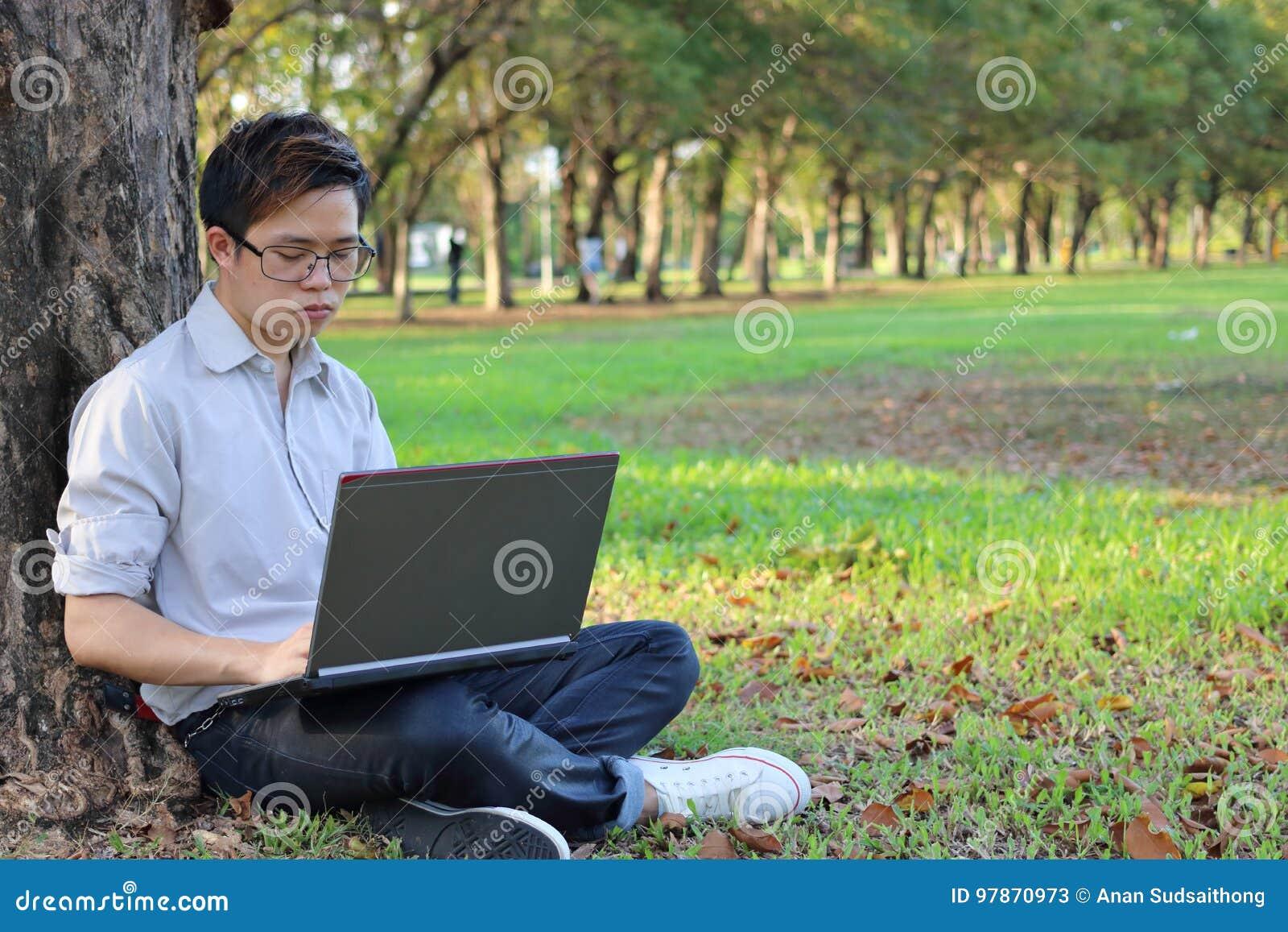 Ståenden av en allvarlig ung affärsman som arbetar på hans bärbar datordator i stad, parkerar med kopieringsutrymmebakgrund
