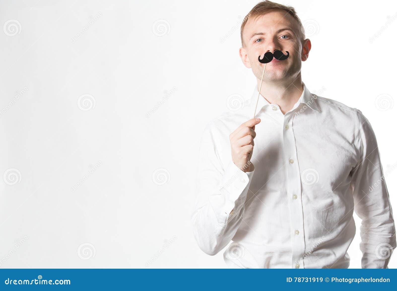 Ståenden av en attraktiv ung man som bär en retro stil, fejkar mustaschen