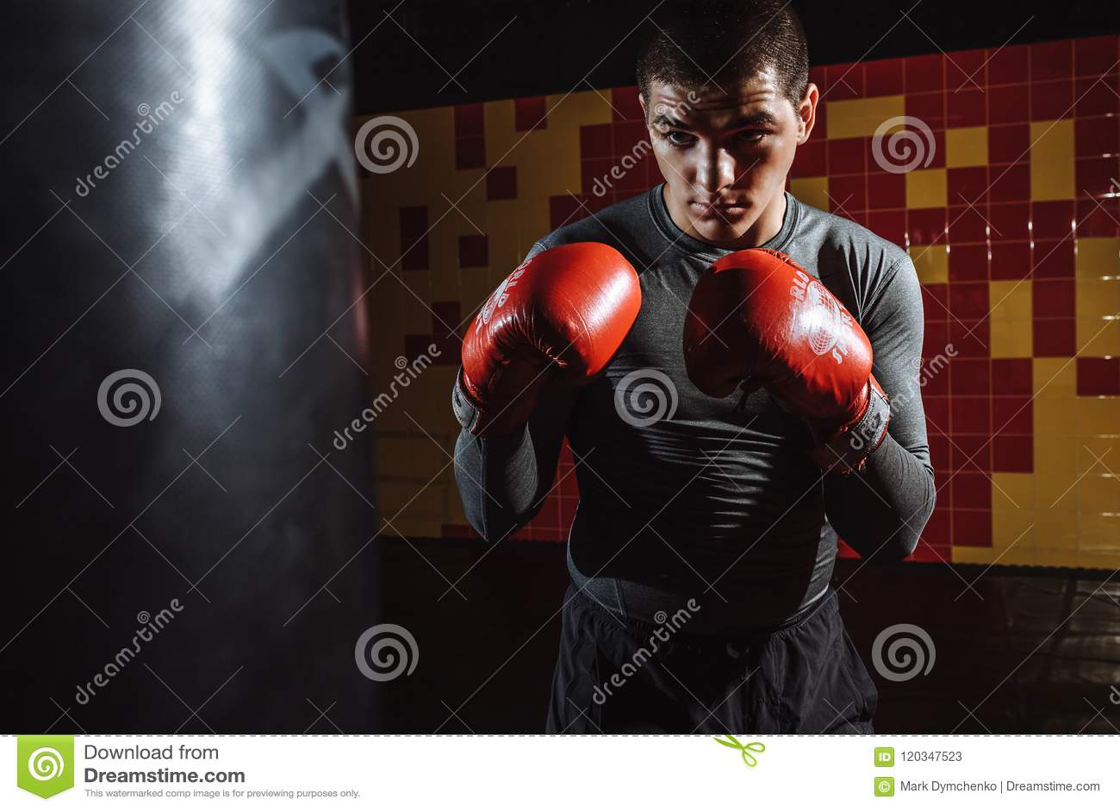 Ståenden av en boxare i idrottshallen, en man ser aggressiv