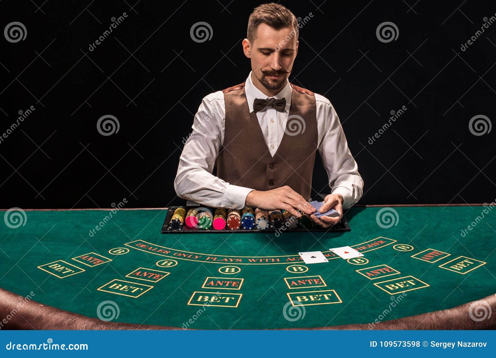 Ståenden av en croupier rymmer att spela kort som spelar gå i flisor på tabellen Svart bakgrund