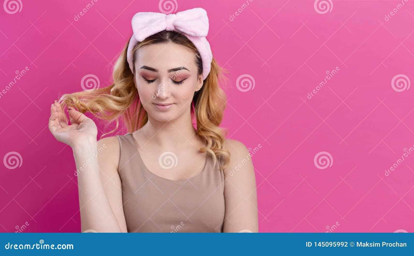 Ståenden av en härlig flickakvinna i en huvudbindel för utgör på en studiobakgrund, begreppet av skönhet som annonserar skönhetsm
