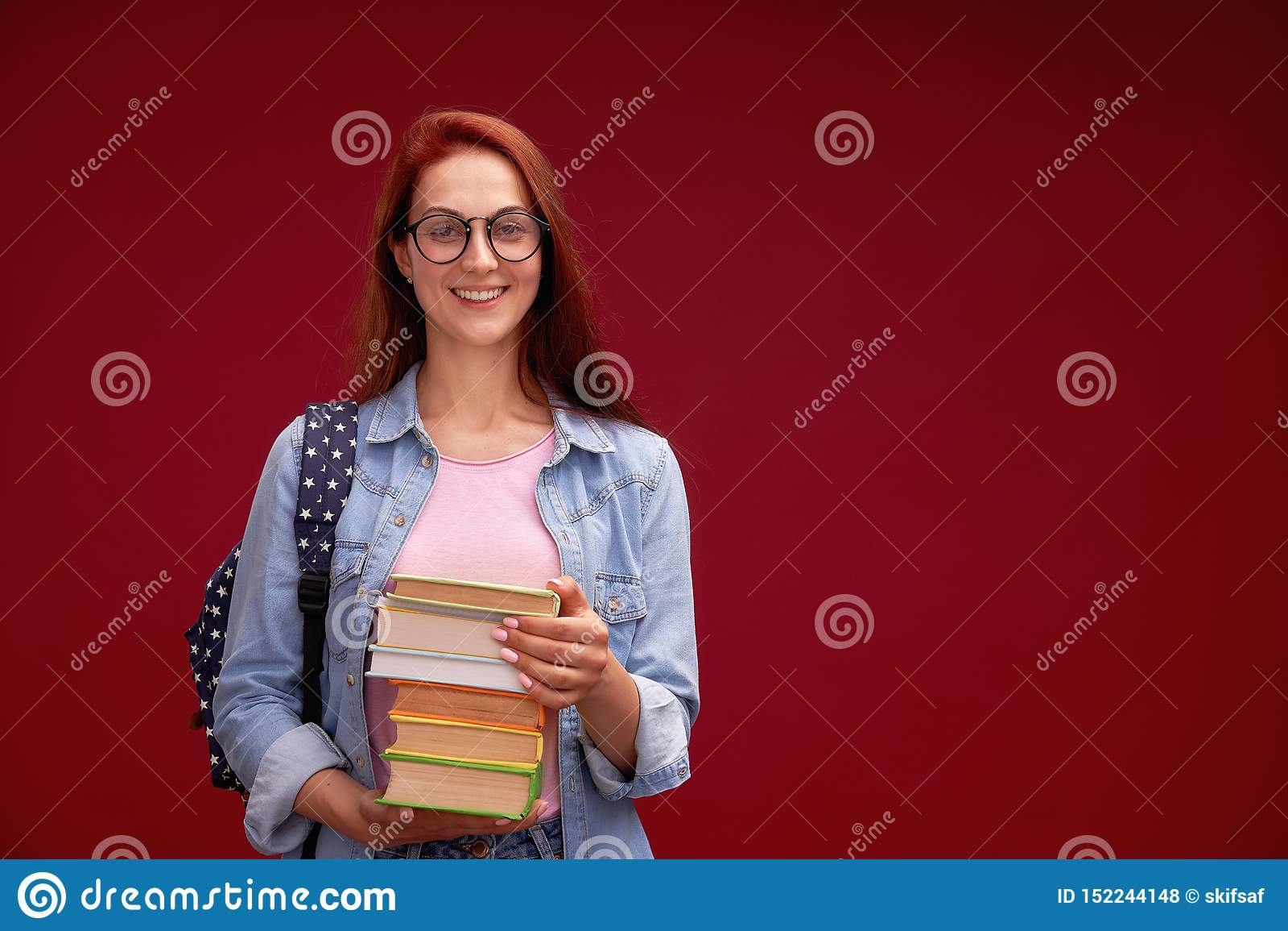 Ståenden av en härlig flickastudent med en ryggsäck och en bunt av böcker i hans händer ler på den röda bakgrunden