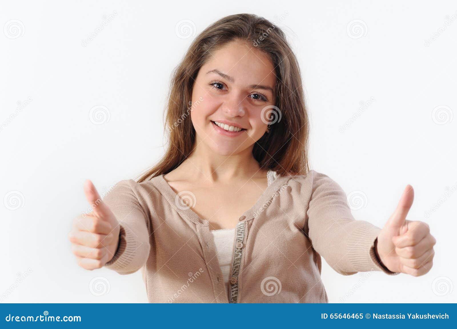 Ståenden av en härlig ung kvinna som ler och rymmer, tummar u
