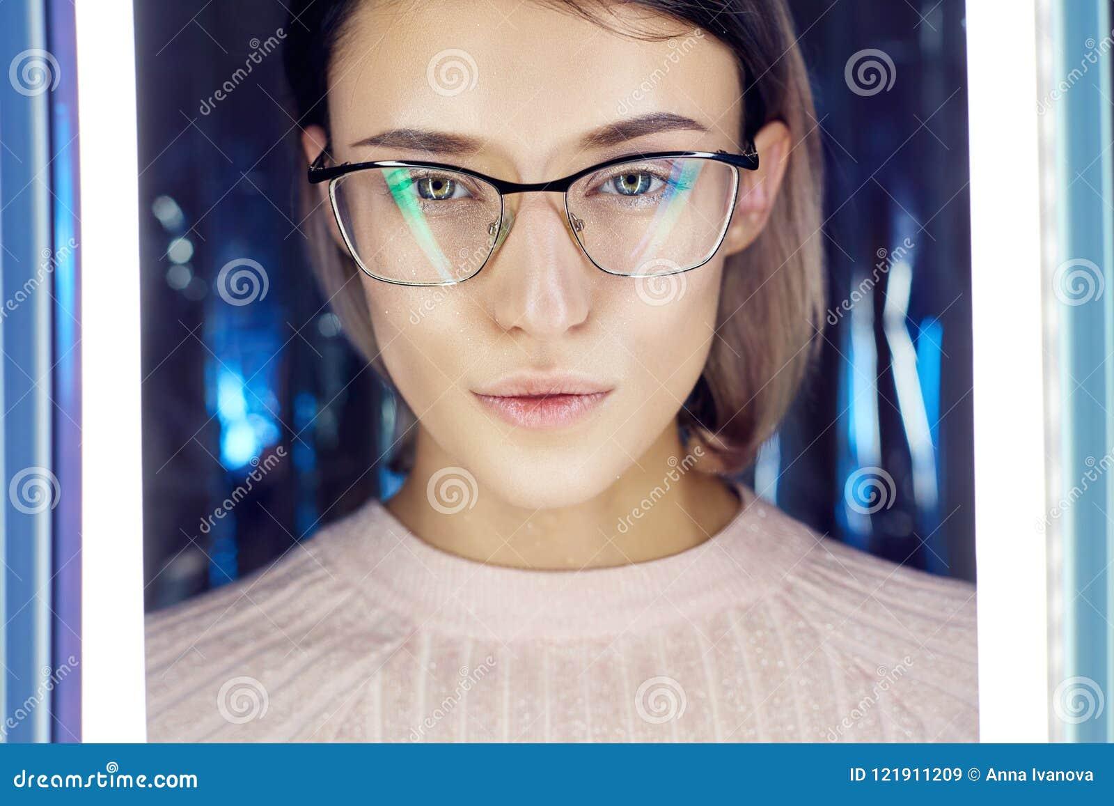 Ståenden av en kvinna i neon färgade reflexionsexponeringsglas i bakgrunden Bra vision, perfekt makeup på flickaframsida Härlig W