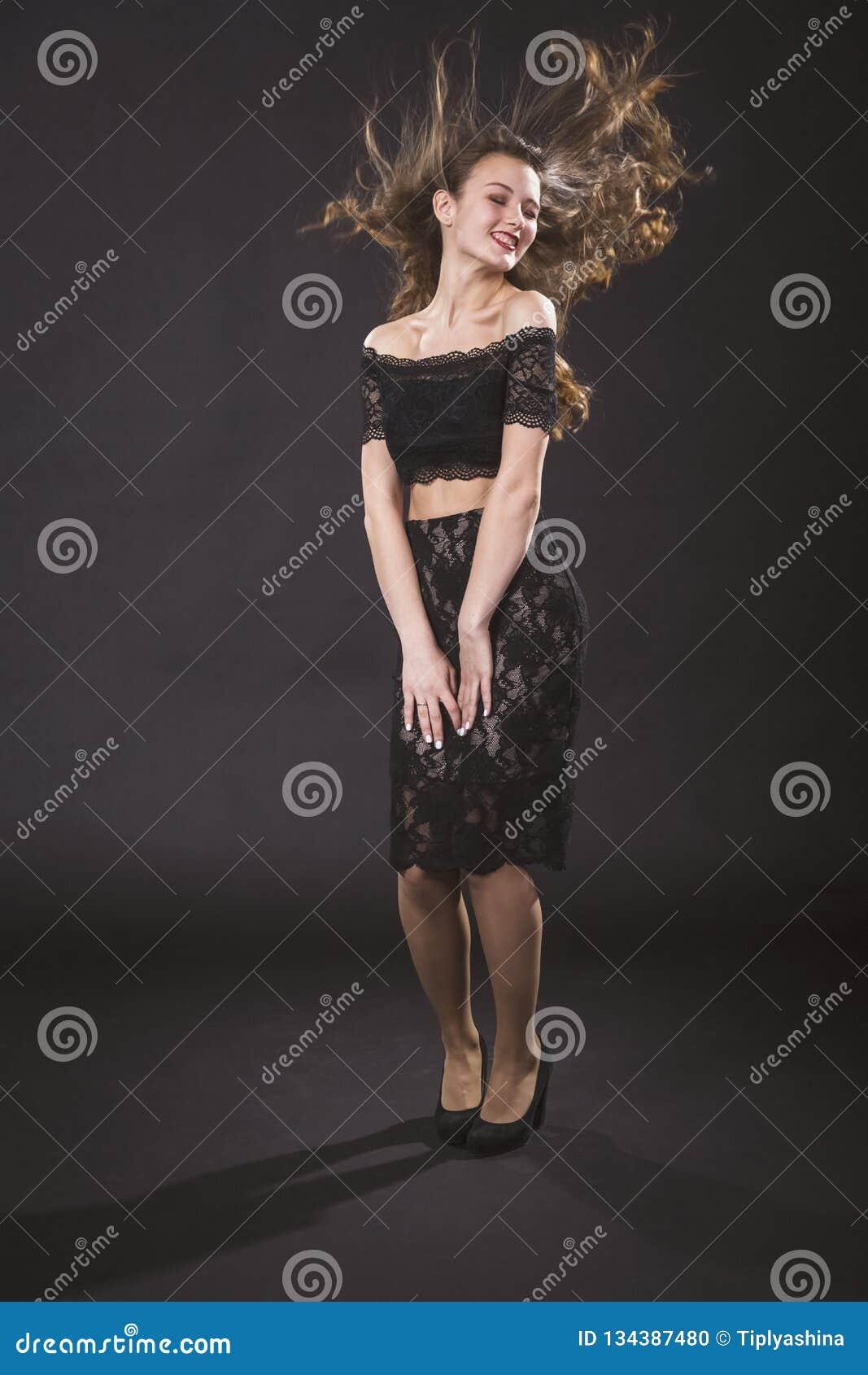 Ståenden av en le ung flicka i snör åt klänningen på en svart bakgrund