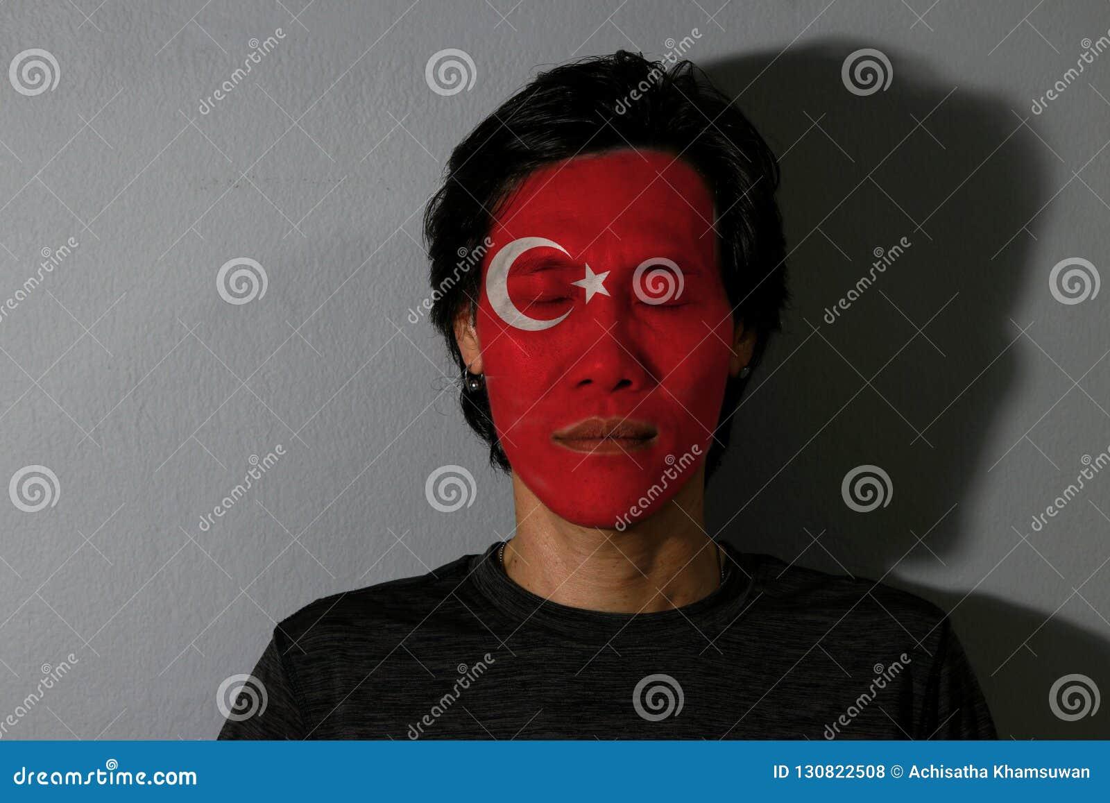 Ståenden av en man med den Turkiet flaggan målade på hans framsida och nära ögon med svart skugga på grå bakgrund